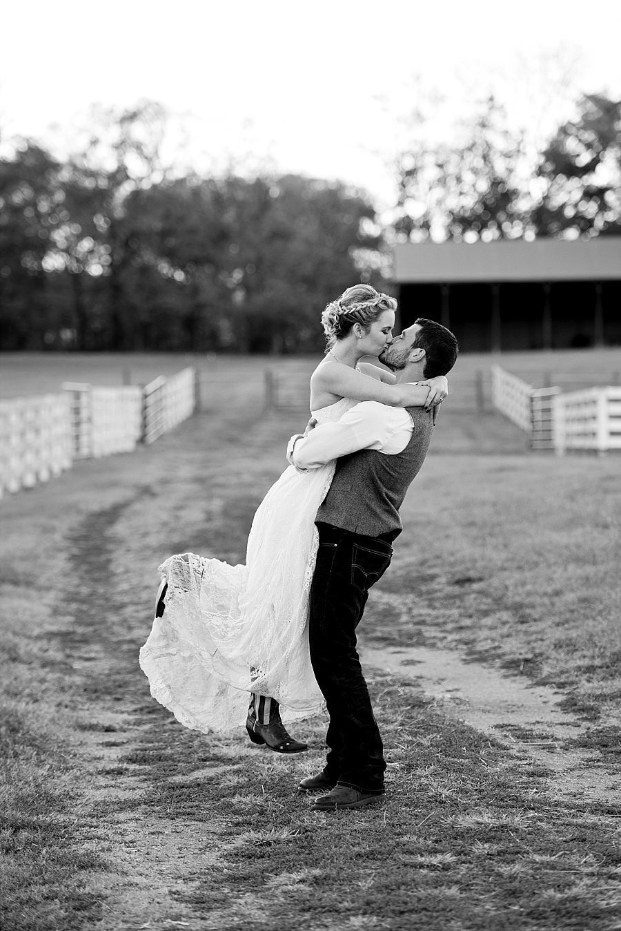 Timeless black and white photo of groom lifting his wife and sharing a kiss with her on the country road