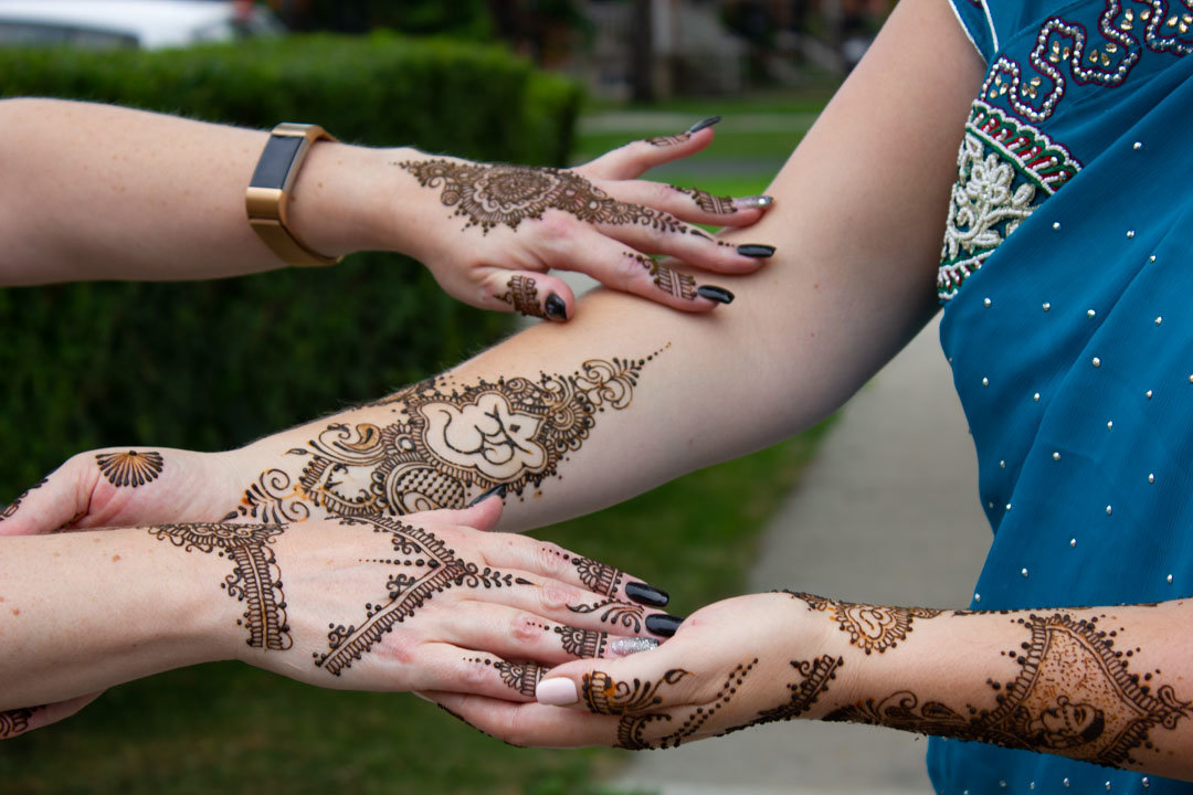 bride displaying her henna tattoo with her friends hands reaching out to hers