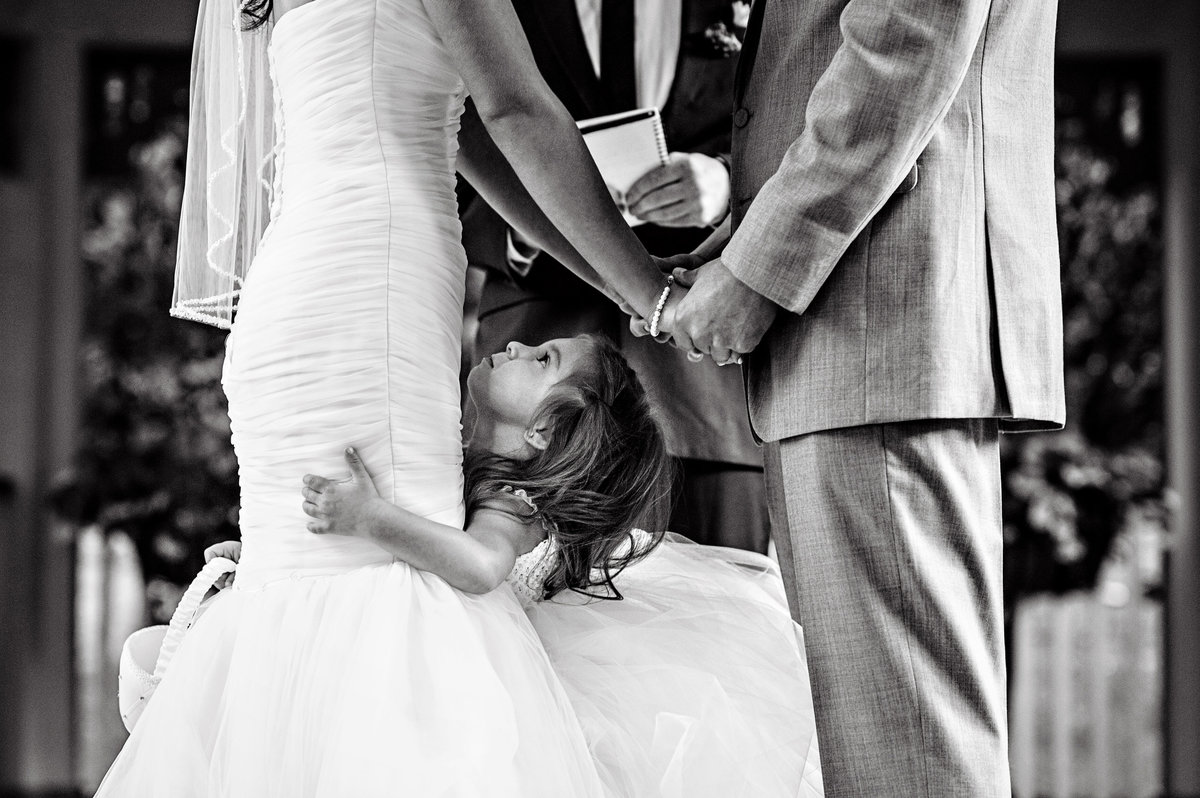 A little girl in between her parents as they get married at Scotland Run Golf Club in New Jersey.