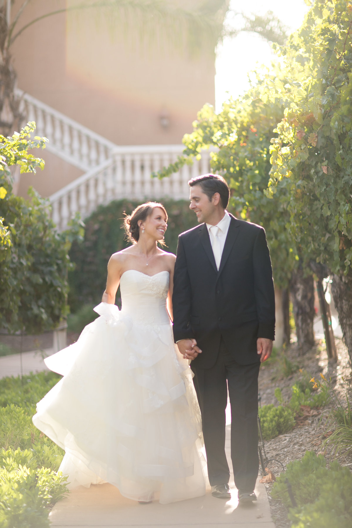 Bride and groom walking through a vineyard in Temecula California