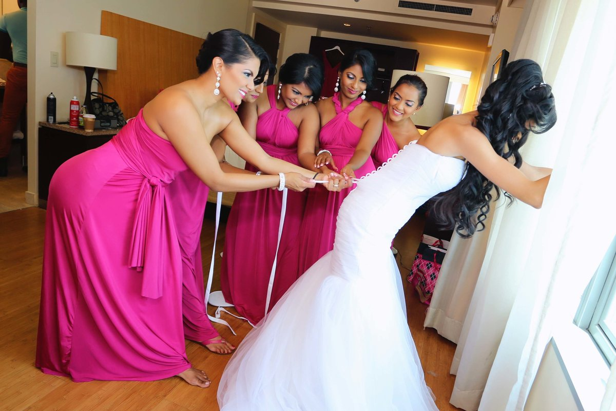 Funny shot of bride being laced into her wedding dress by bridal party wearing pink dresses. Photo by Ross Photography, Trinidad, W.I..