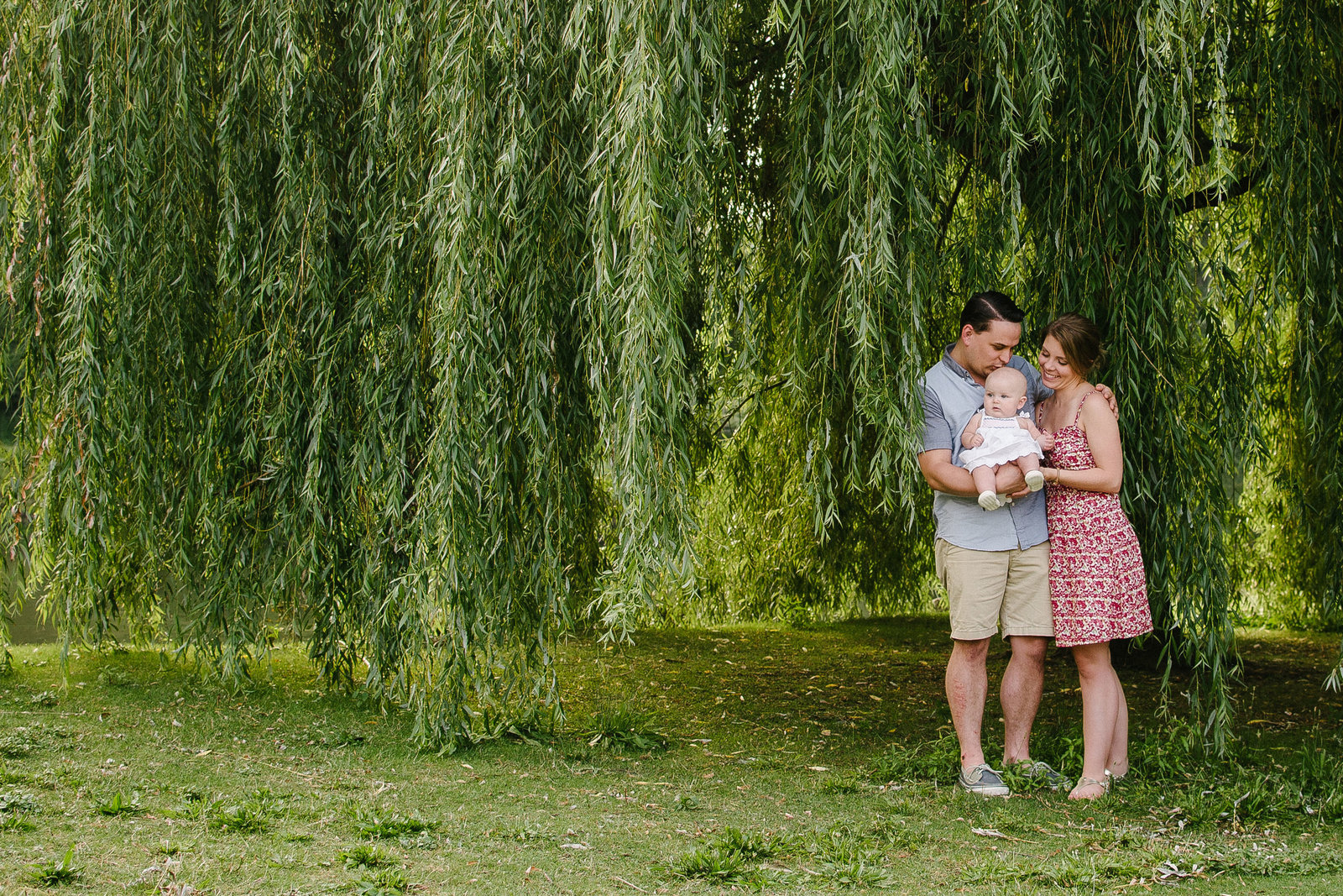 parents holding daughter standing under willow tree