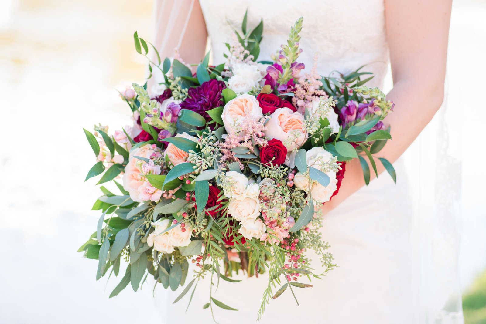 Wild Bunches Floral Wedding Bouquet in burgundy and blush held by a bride at twisted ranch