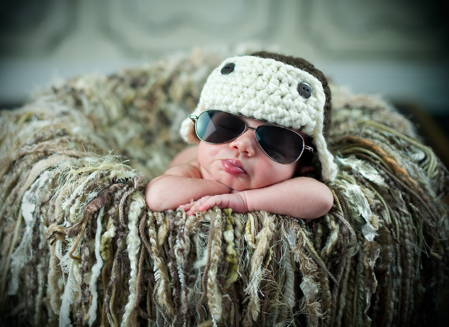 newborn baby posing with aviator sunglasses and crochet hat