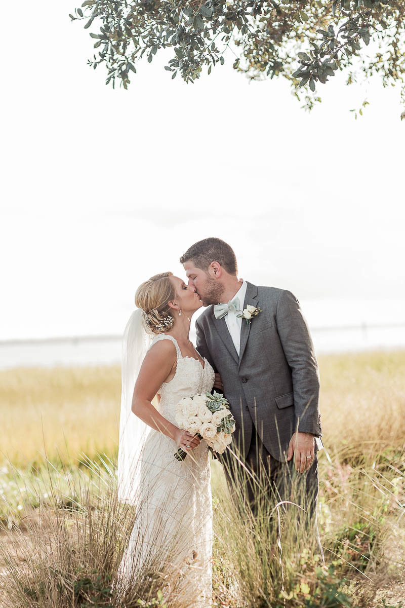 Bride and groom stand in tall grass, Alhambra Hall, Mt Pleasant, South Carolina