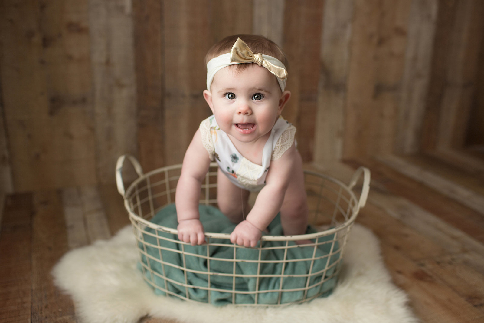 little girl poses for baby photo on wood backdrop