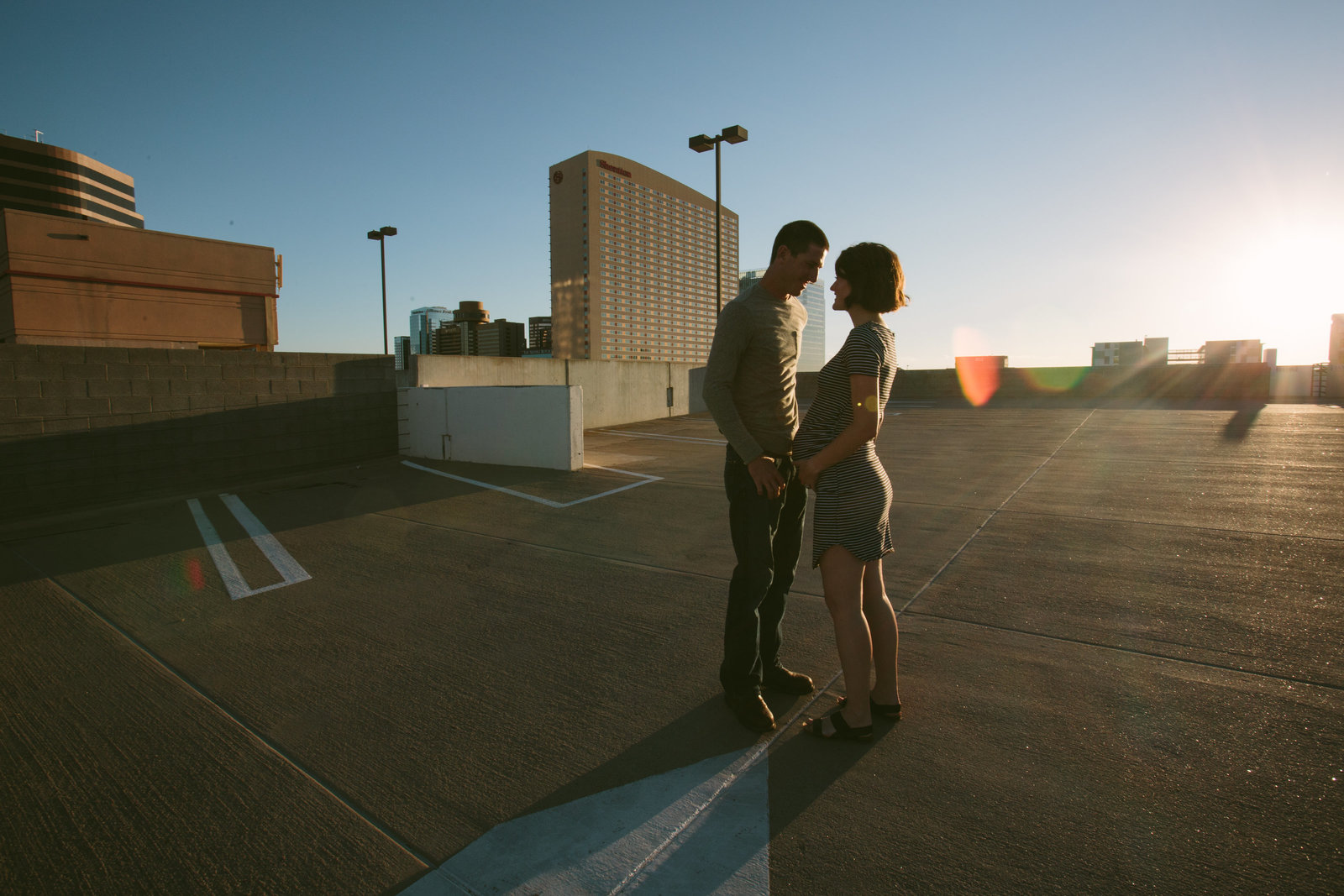 An expecting couple in a parking garage at sunset