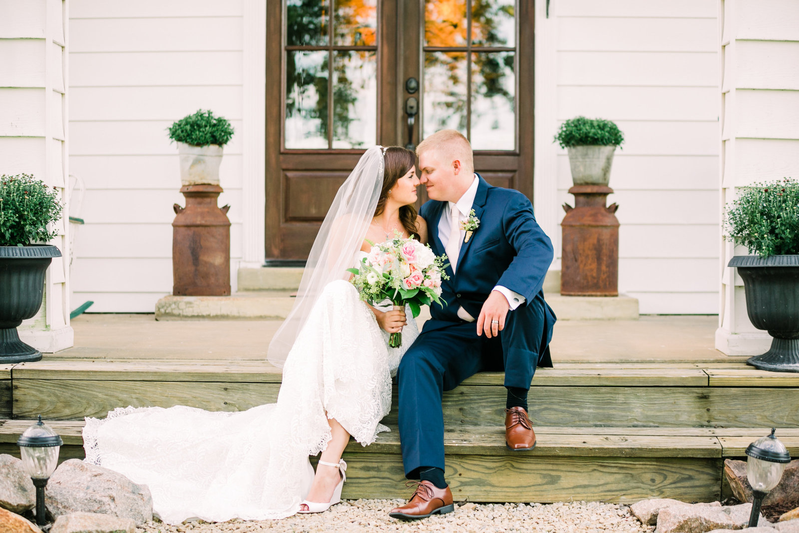 Bride and Groom, Liz and Tyler, sit for a photo in front of the big white house at Dodson Orchards by Jackelynn Noel Photography