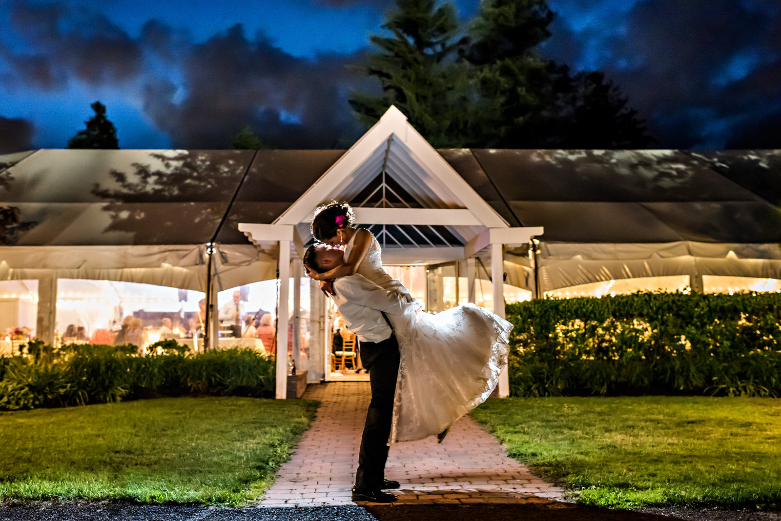A groom lifts his bride up in the air in front of their reception tent at Pearl S Buck Estate in bucks county.