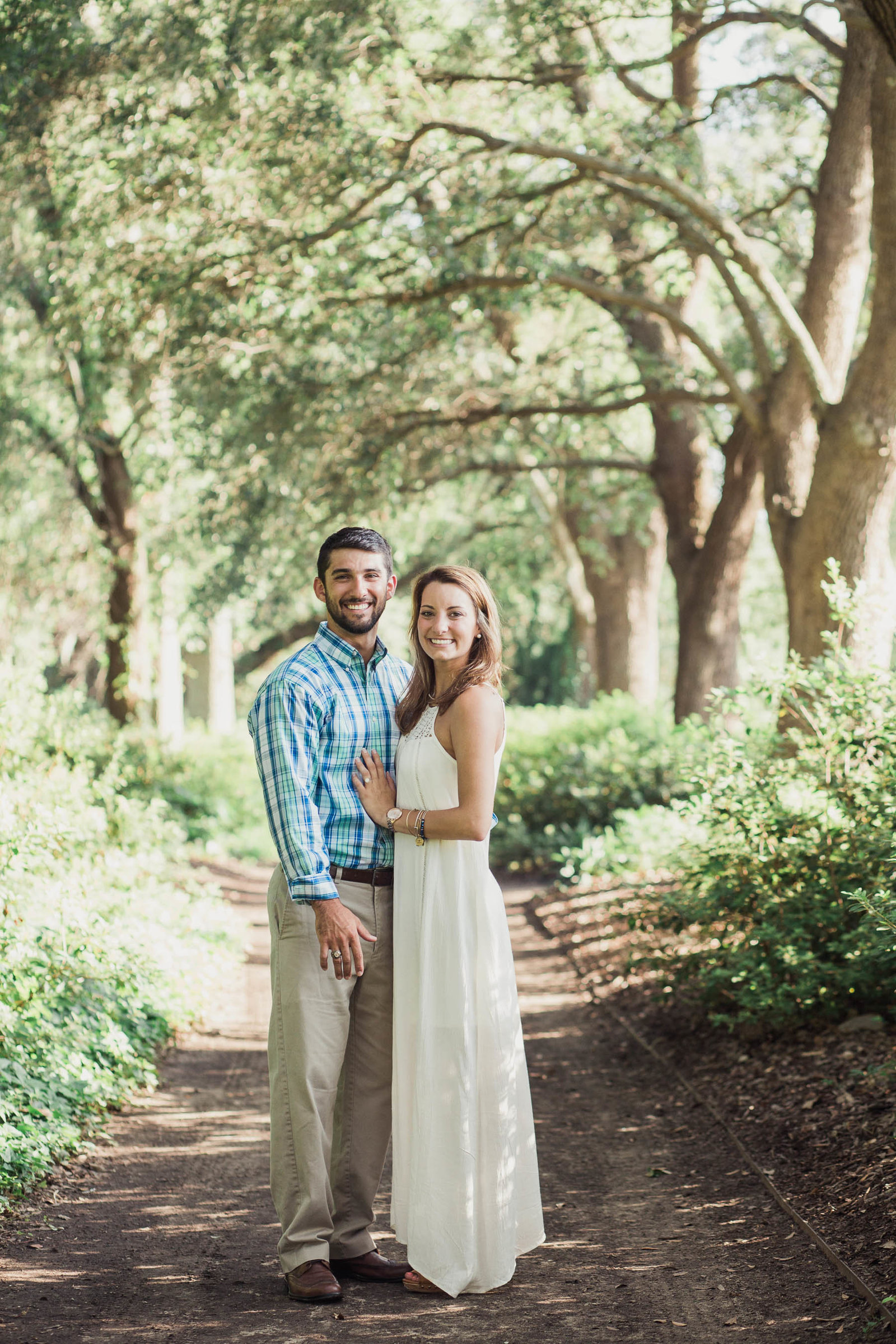 Engaged couple stand in path of oak trees, Hampton Park, Charleston, South Carolina
