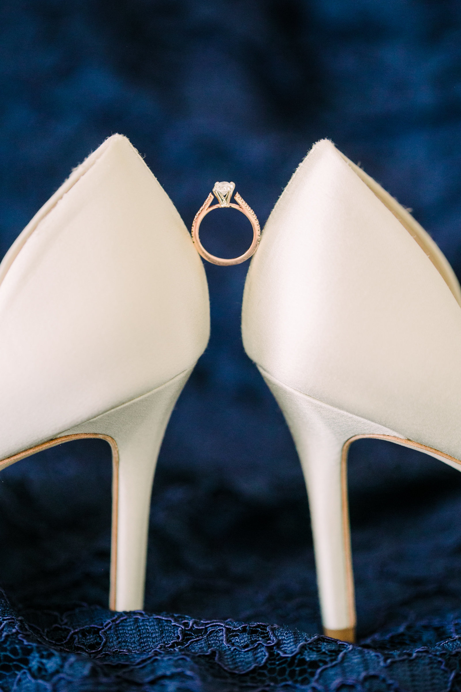 The brides engagement ring is balanced between the heels of her white wedding shoes.