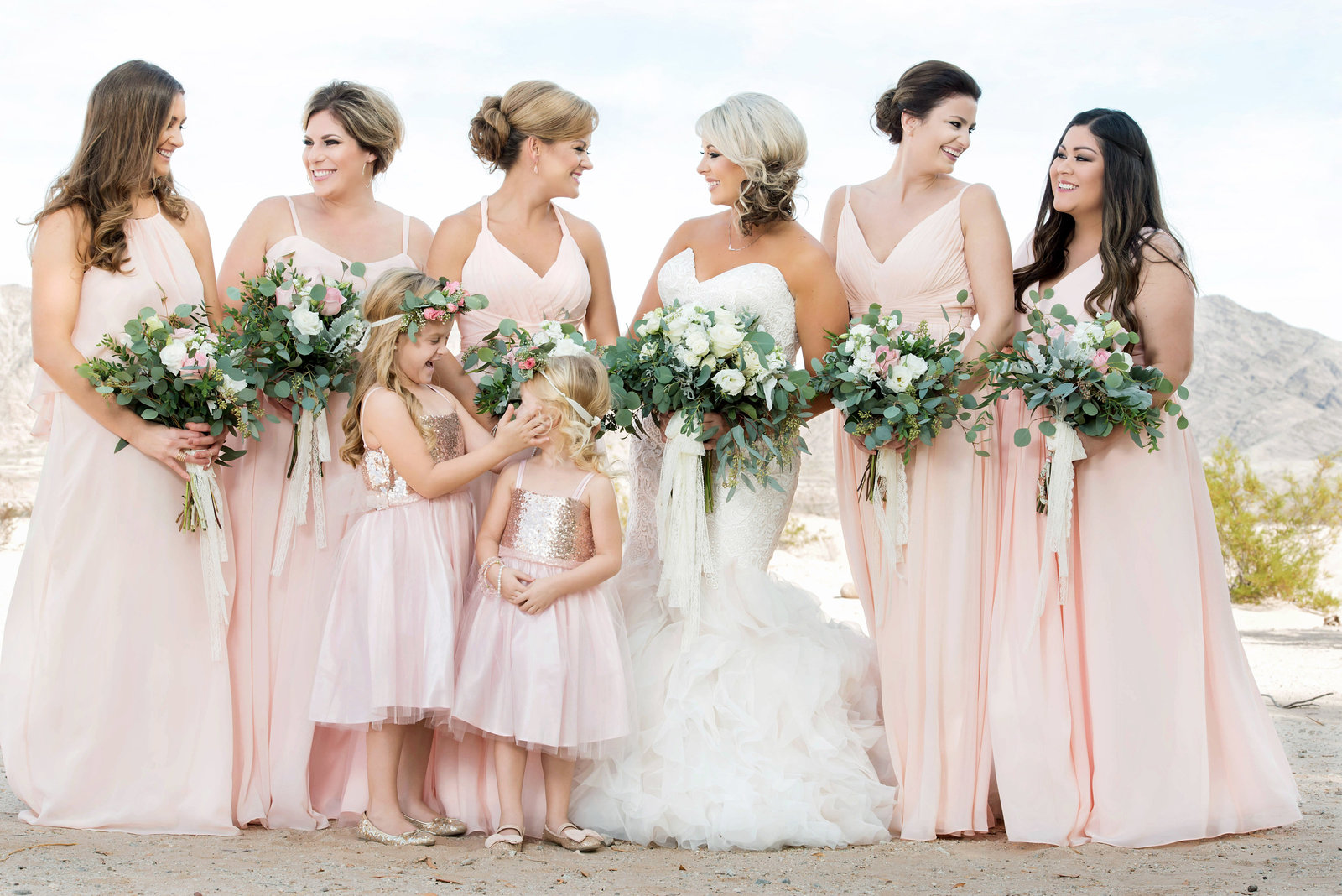 bride with bridesmaids standing in the desert