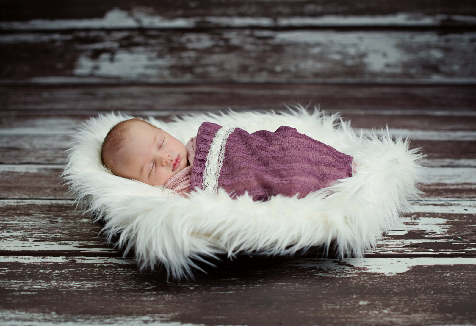 image of newborn in faux fur with rustic wood background