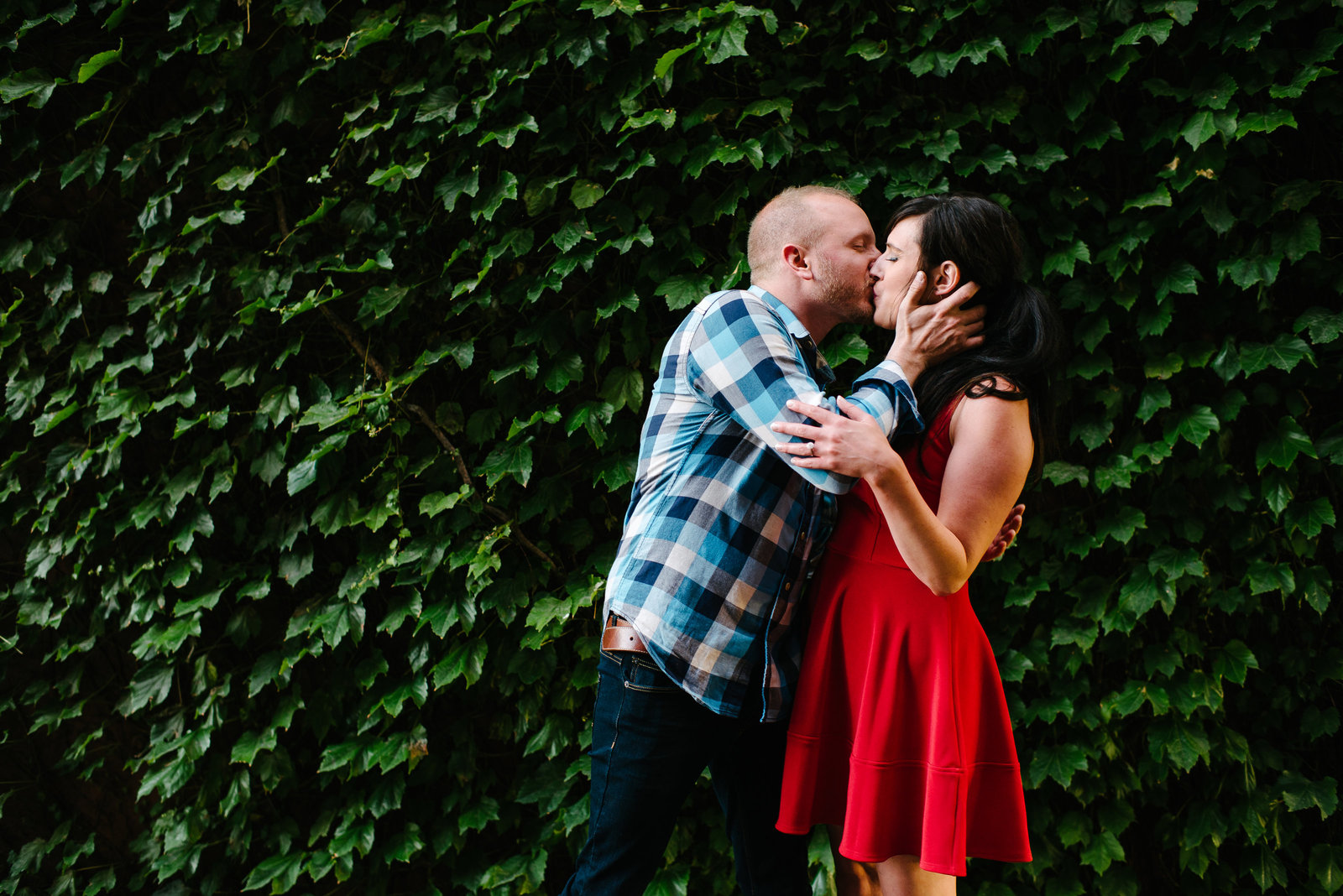 Cleveland OH man in blue plaid shirt woman in red dress kissing in front of green ivy