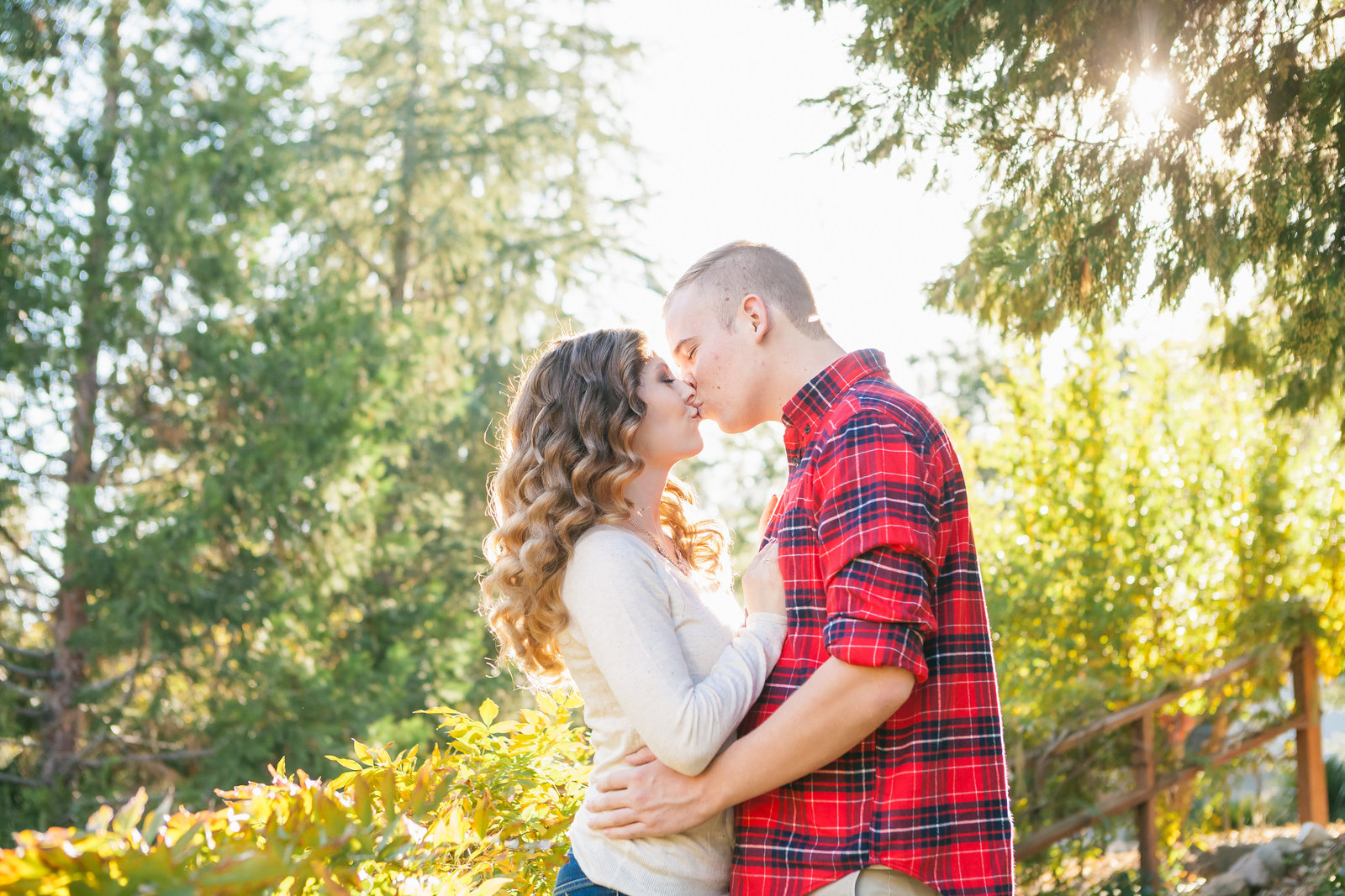 Auburn engaged couple kissing, natural light