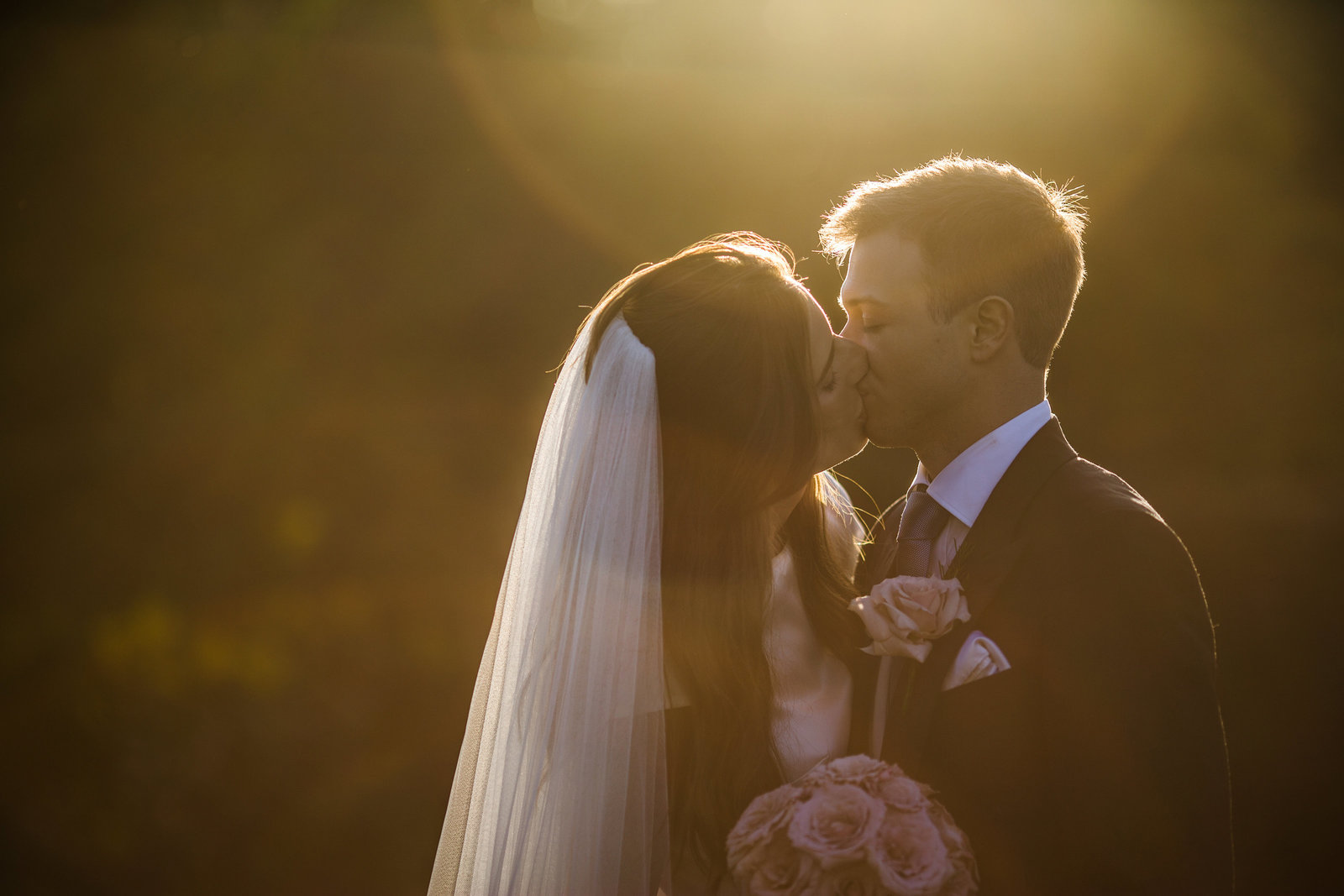 Beautifully lit bride and groom and sunkissed with sunflare as they share a kiss for this couple portrait during golden hour at Pangdean Barn in East sussex