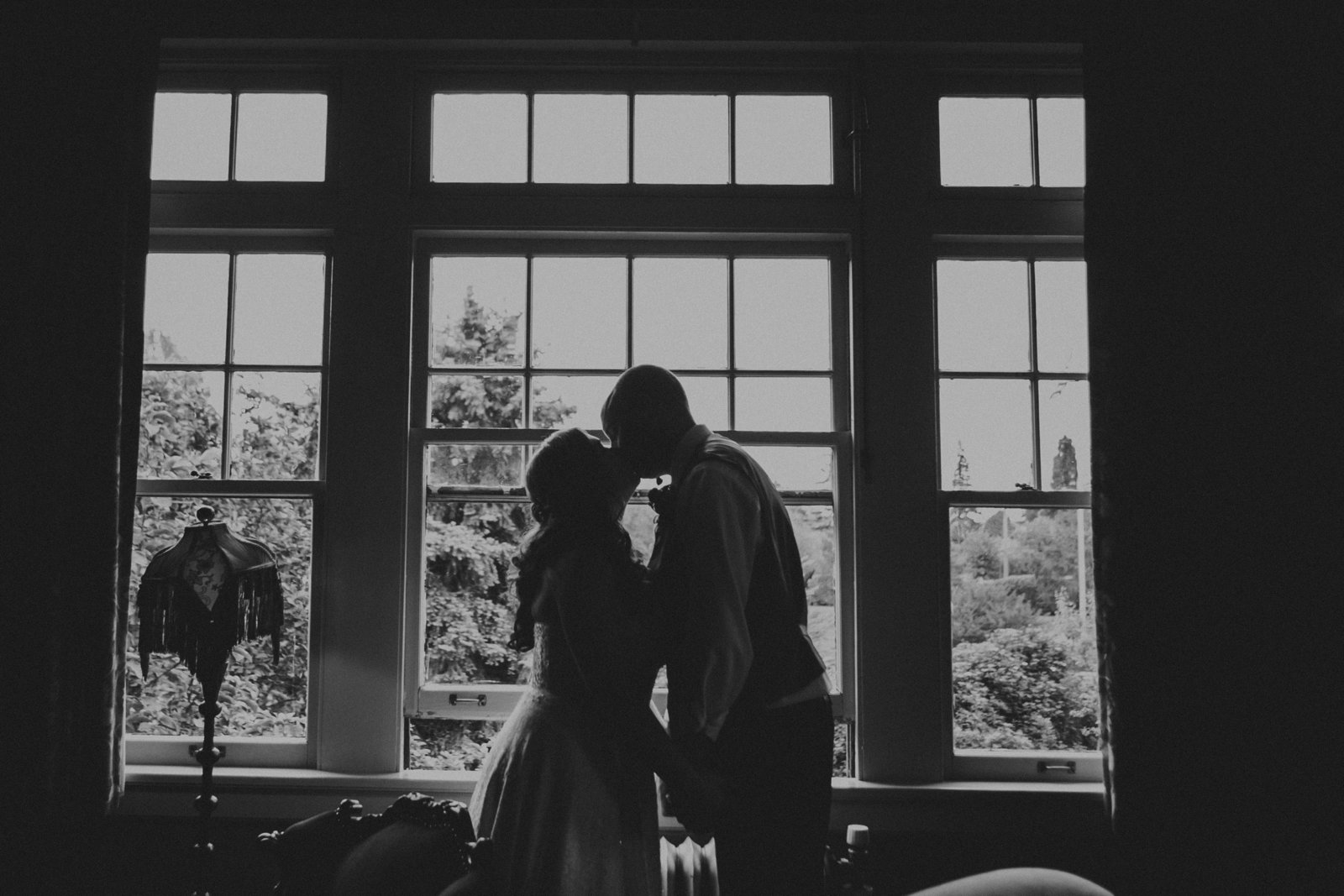 black and white photo of bride & groom kissing inside the McMenamins Grand Lodge in Forest Grove, OR | Susie Moreno Photography