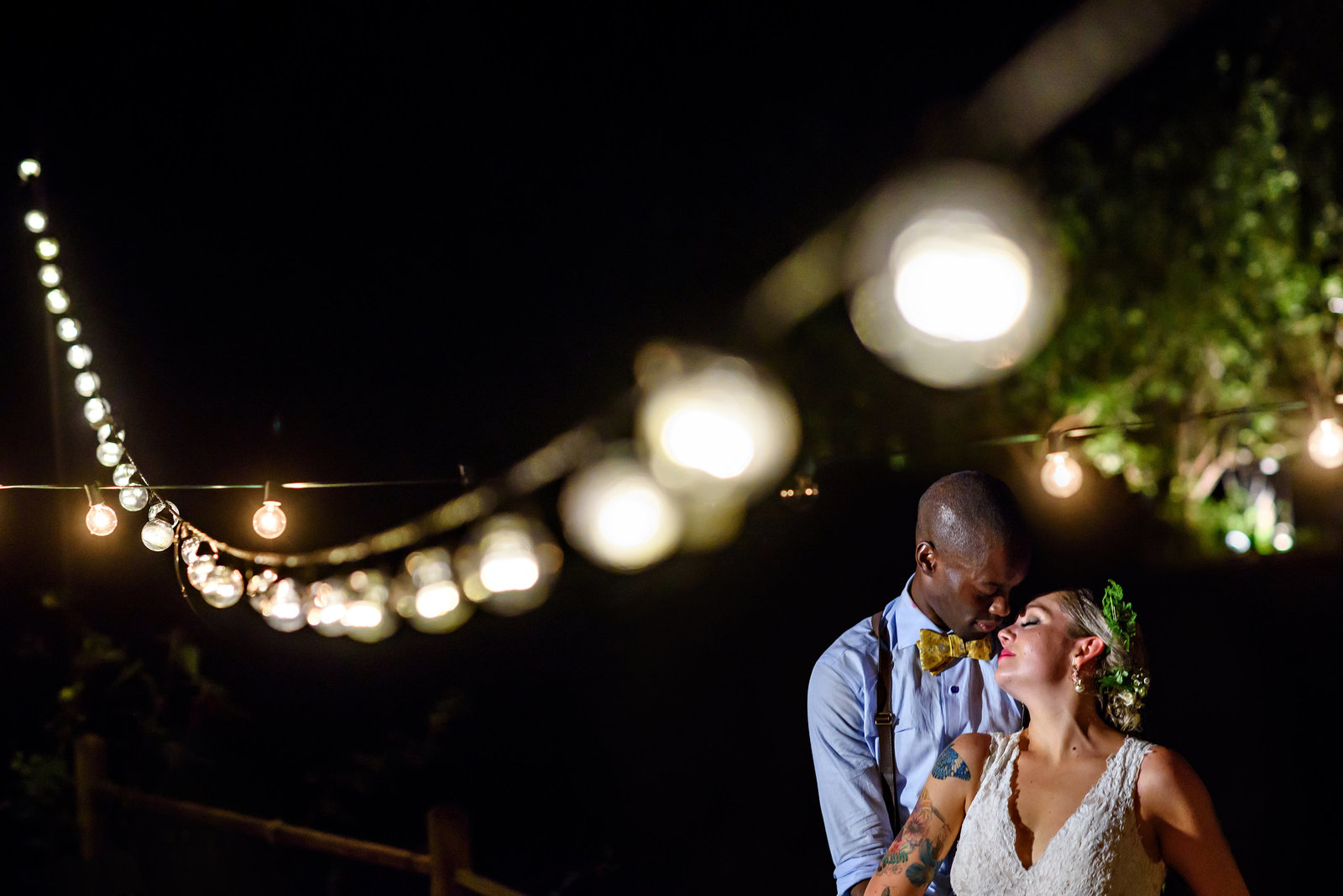A wedding couple kiss under the string lights at their Baltimore Wedding.