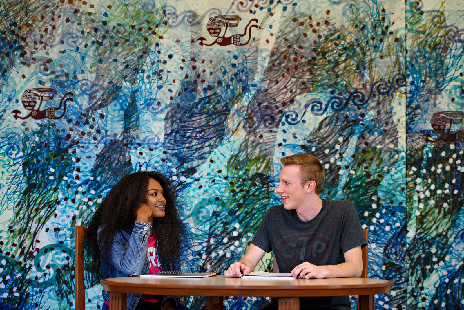 A study session between two students in front of a large painting in a college library.