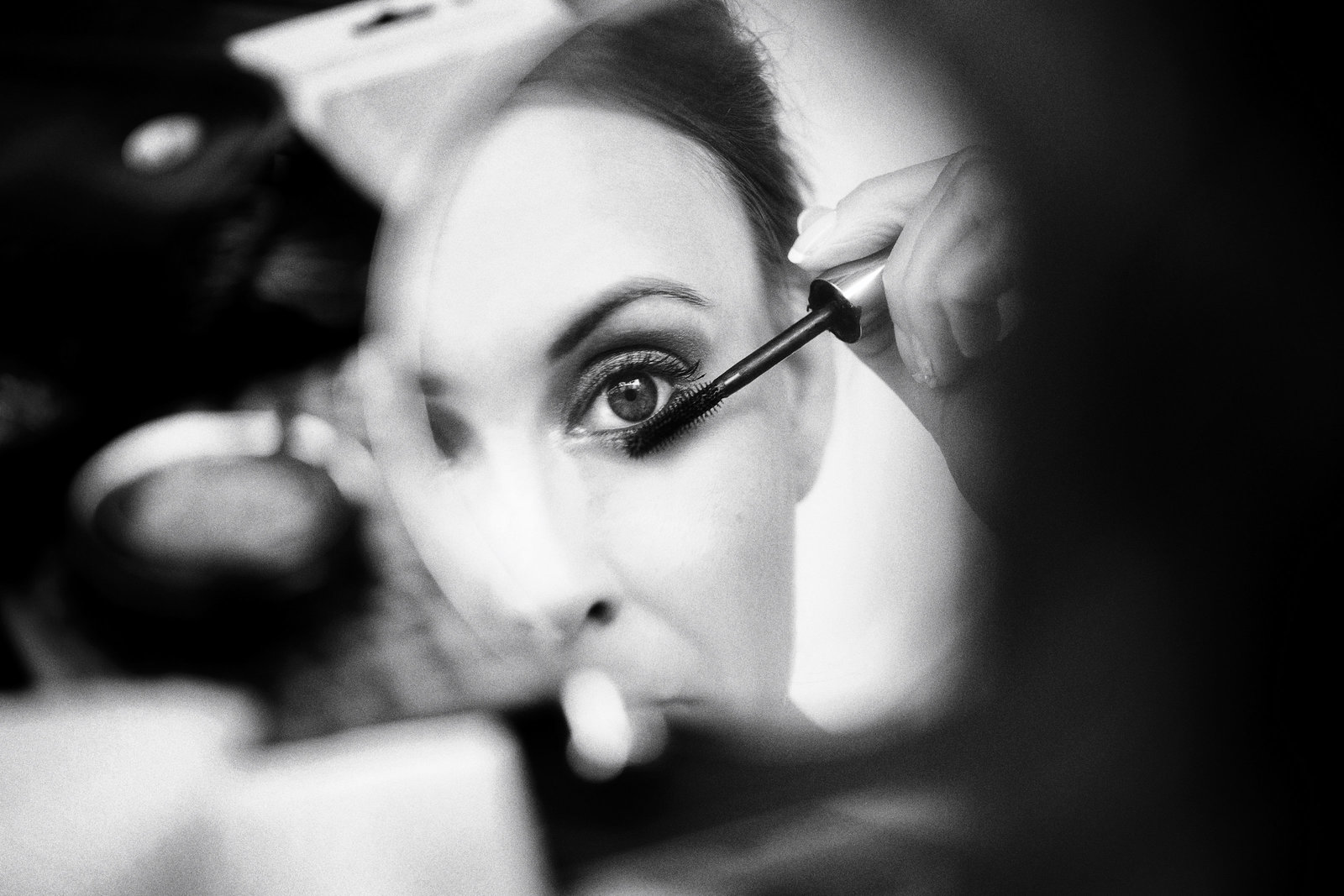 A favourite wedding photo in black and white of a bride close up putting mascara on in the mirror. The photo is the reflection in the mirror taken at an amazing wide aperture of f1.2 on a 50mm lens