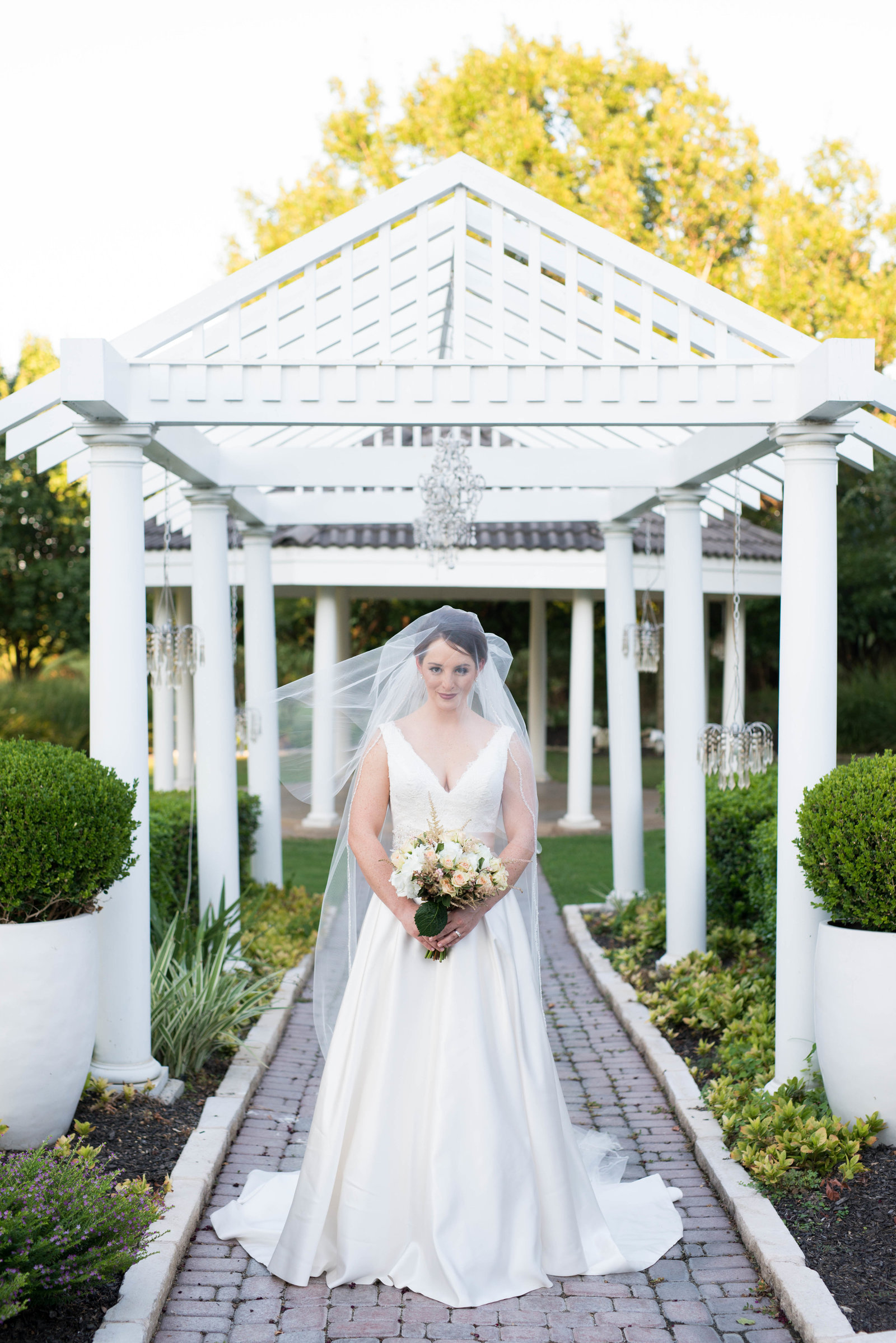 Bride stands under walkway of the Plantation House in Pflugerville with wedding veil draped overhead