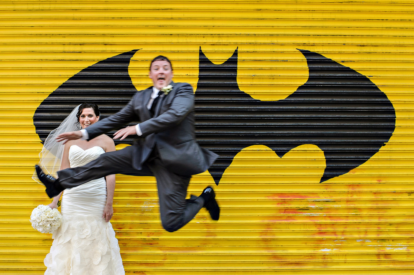 A wedding couple jump for love in front of batman graffiti on South Street in Philadelphia.