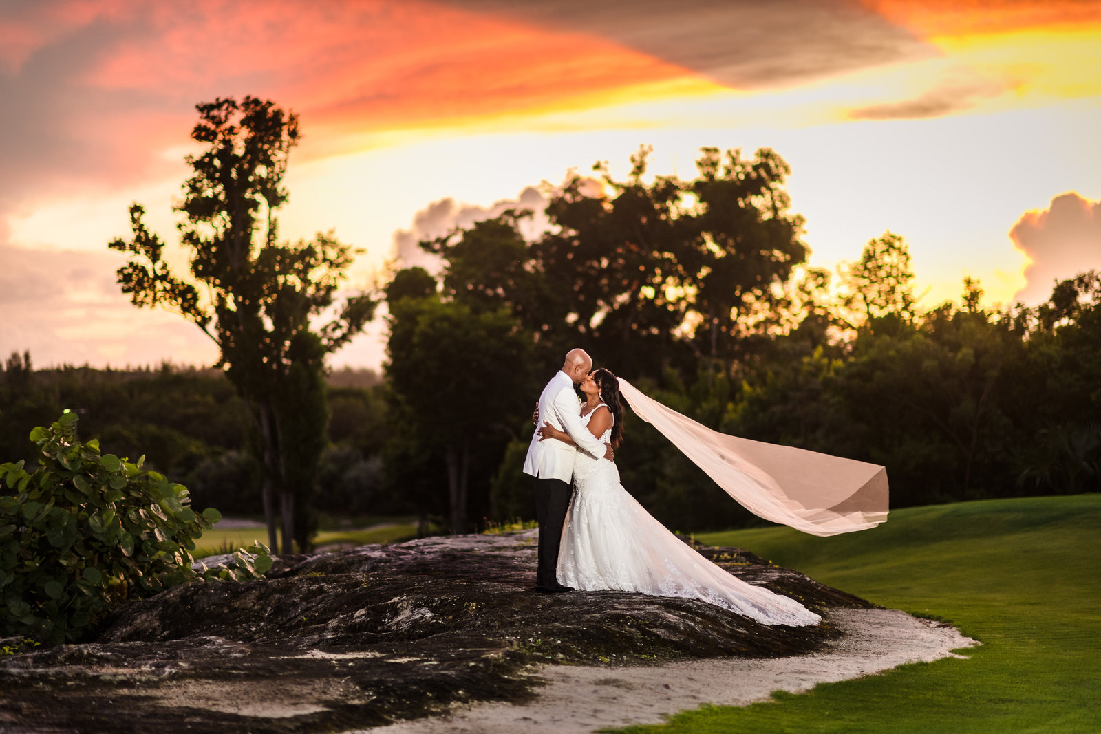 Bride with veil kissing grrom at sunset in the bahamas at Royal blue golf course