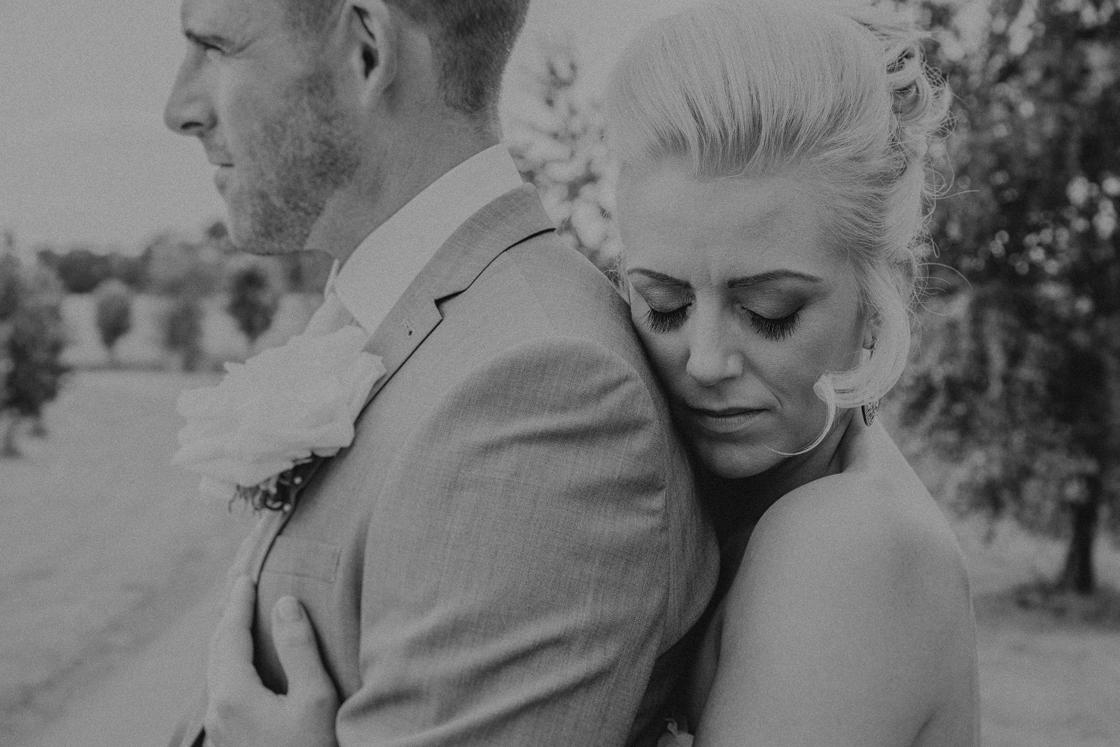 Bride hugging groom from behind as he looks out over fields by Leeds Wedding Photographer Jono Symonds