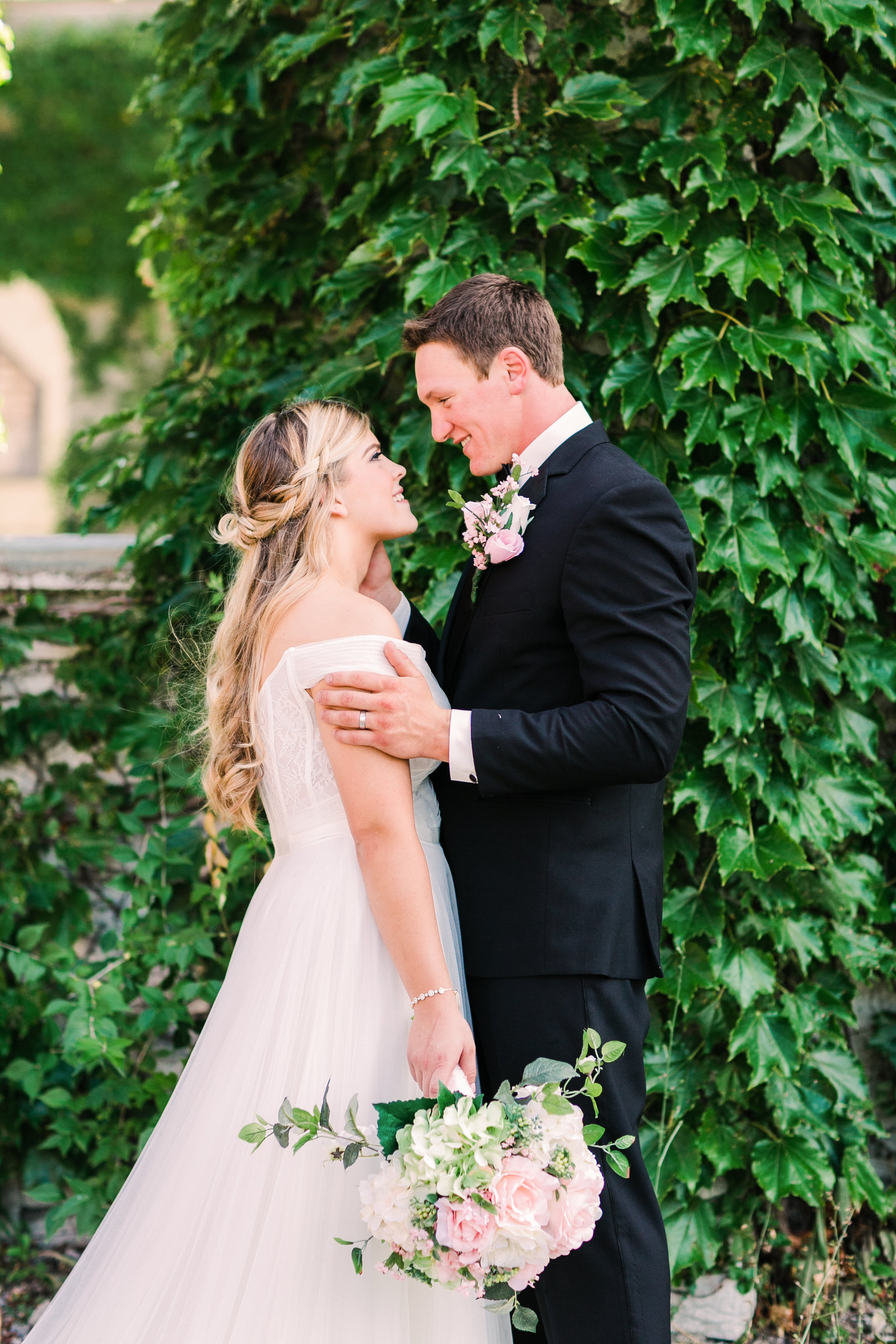 Groom, Levi, gazes at his bride, Katlyn, while embracing her next to an ivy covered wall.