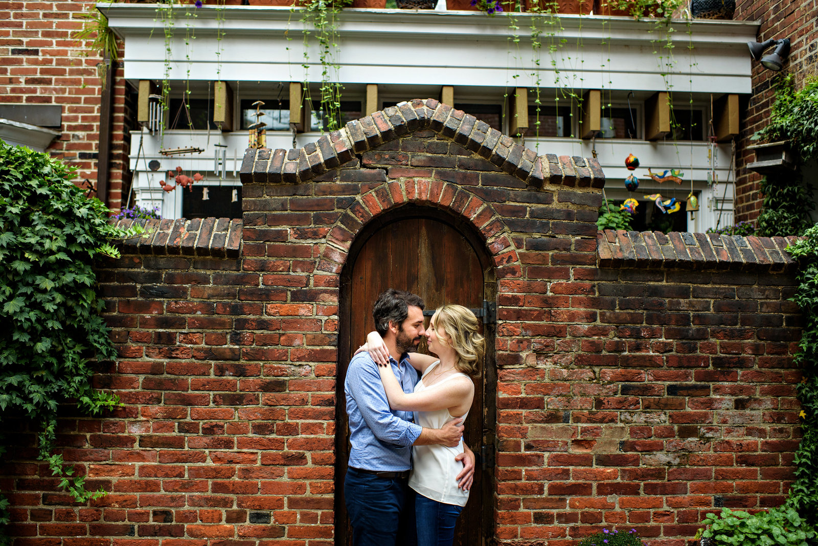 A couple in love with each other are framed in the doorway of a rowhome in center city philadelphia.
