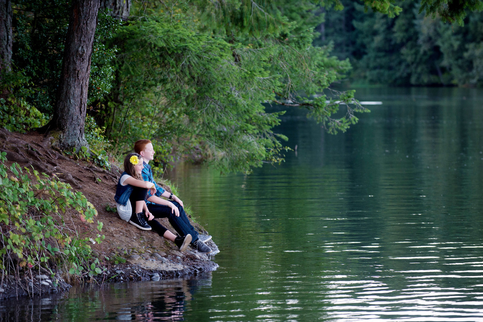 a brother and sister sit on the side of lacamas lake