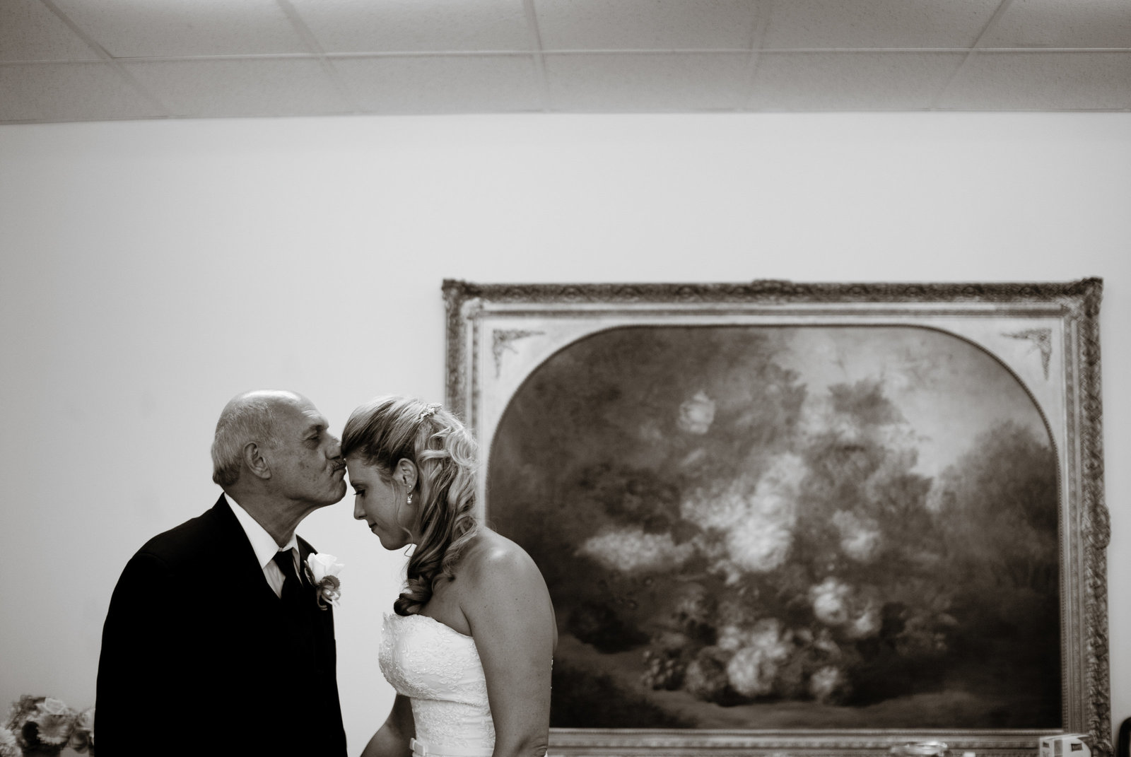 father of bride kisses her head before wedding