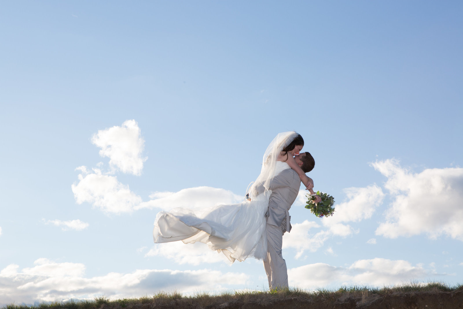 Groom lifting bride into air during wedding photo shoot