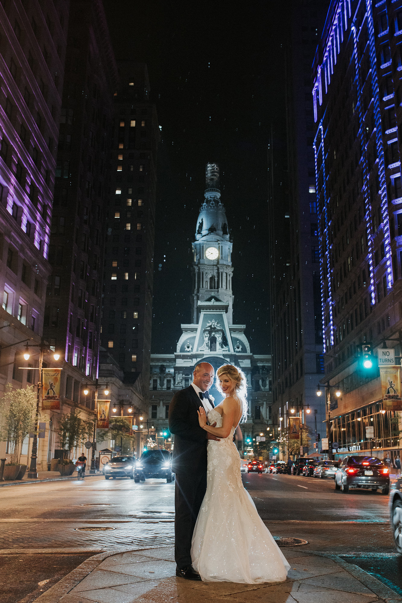 bride and groom outside philadelphia city hall at night