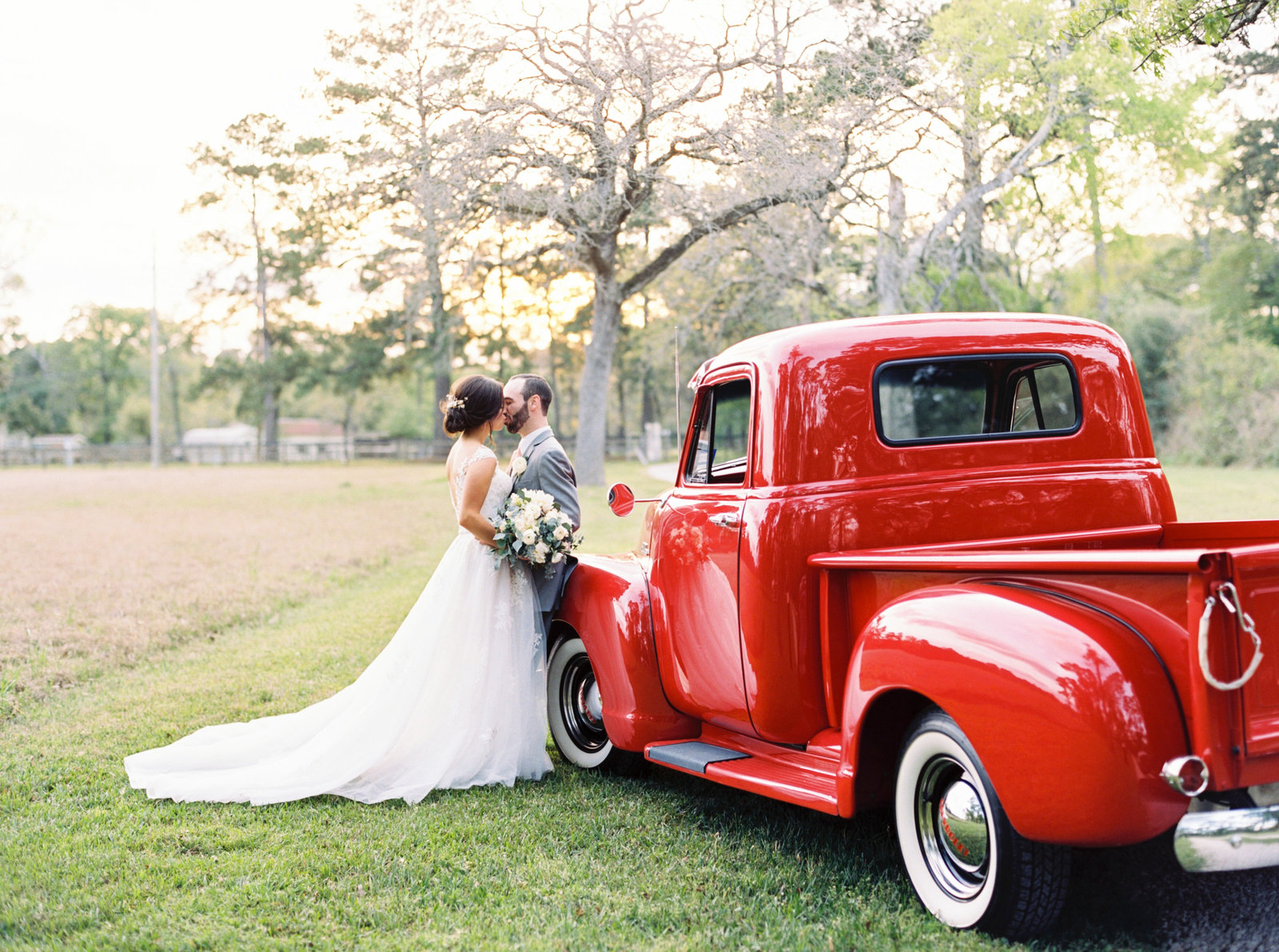 Vintage Red Truck at a Houston Texas wedding with bride and groom kissing.