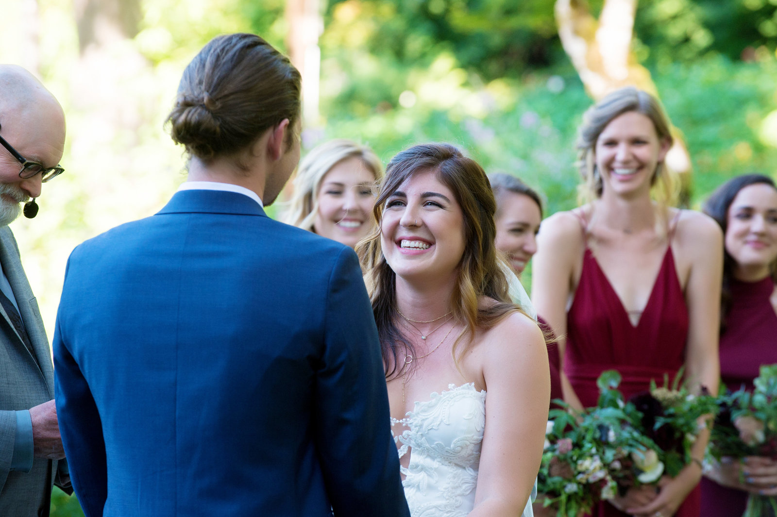 bride and bridesmaids laugh at groom during ceremony