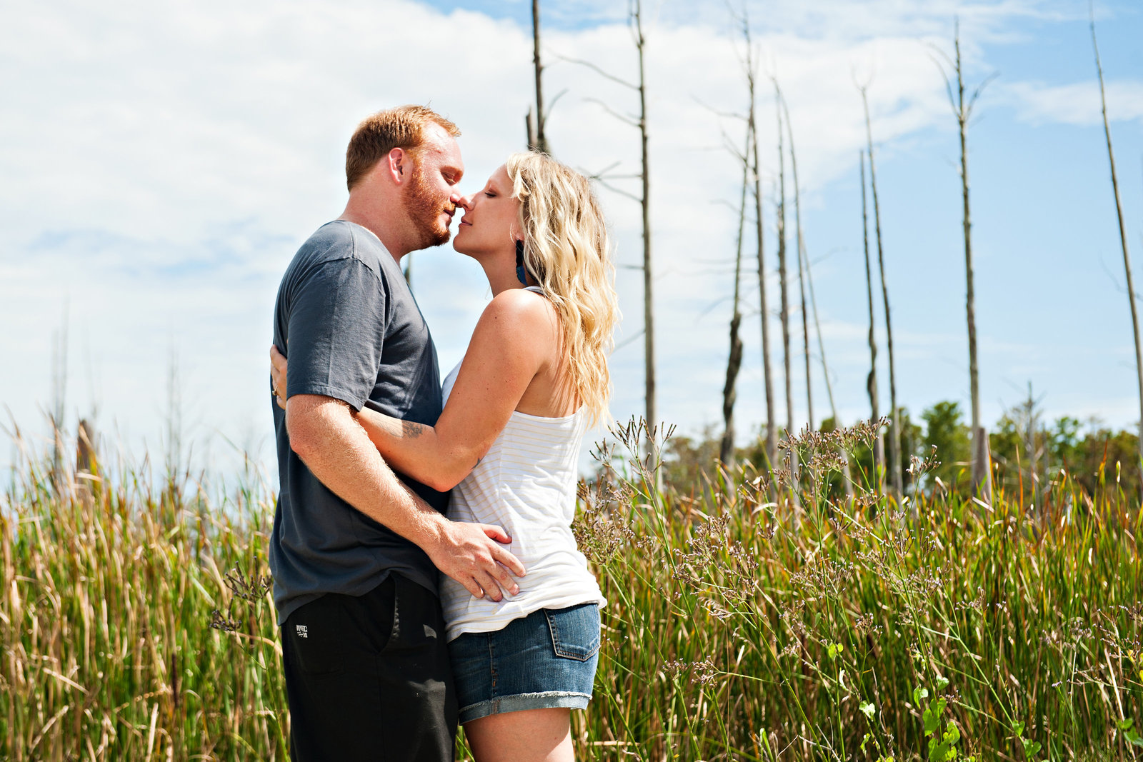 A couple kiss in the north carolina marsh land.