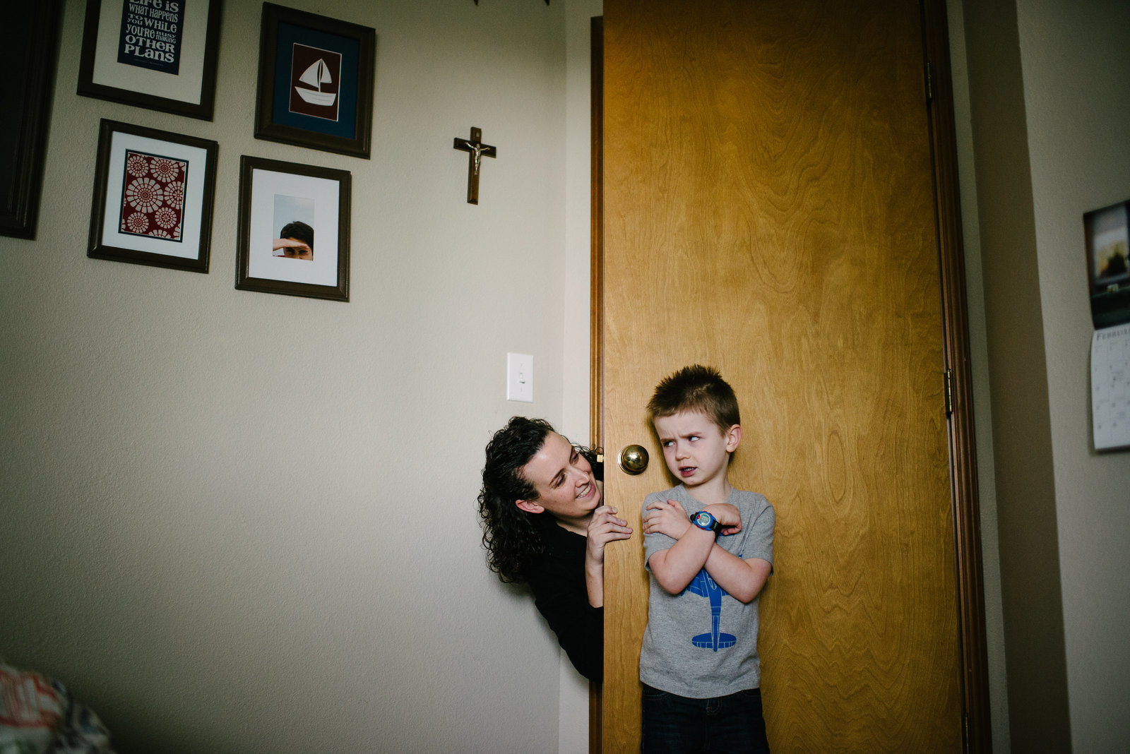 little boy pouting in room as mom peers around door