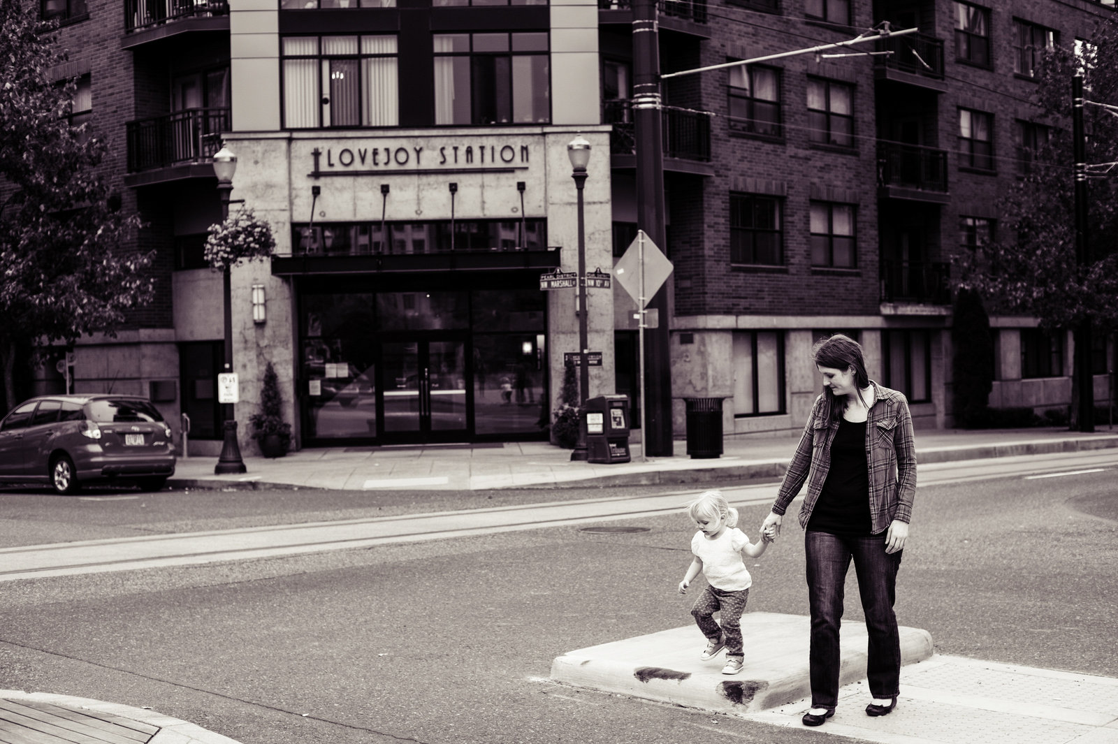 a mom and daughter walk across the street in the pearl district