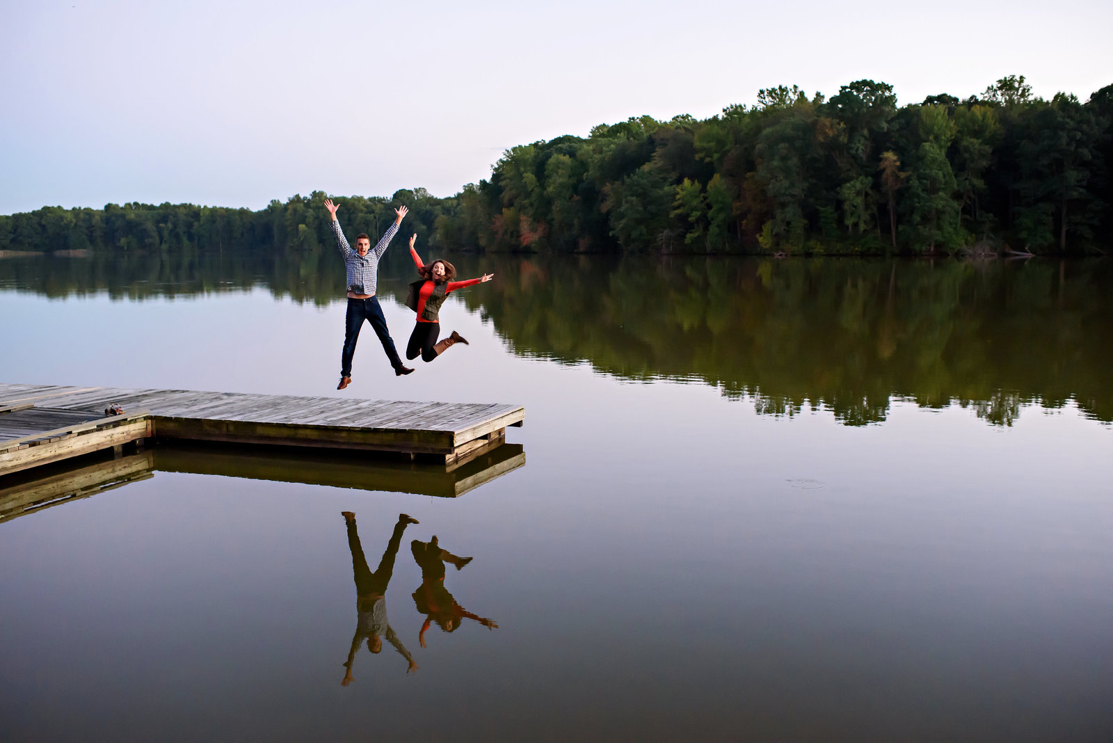 An engaged couple jump at the end of a dock on a lake.