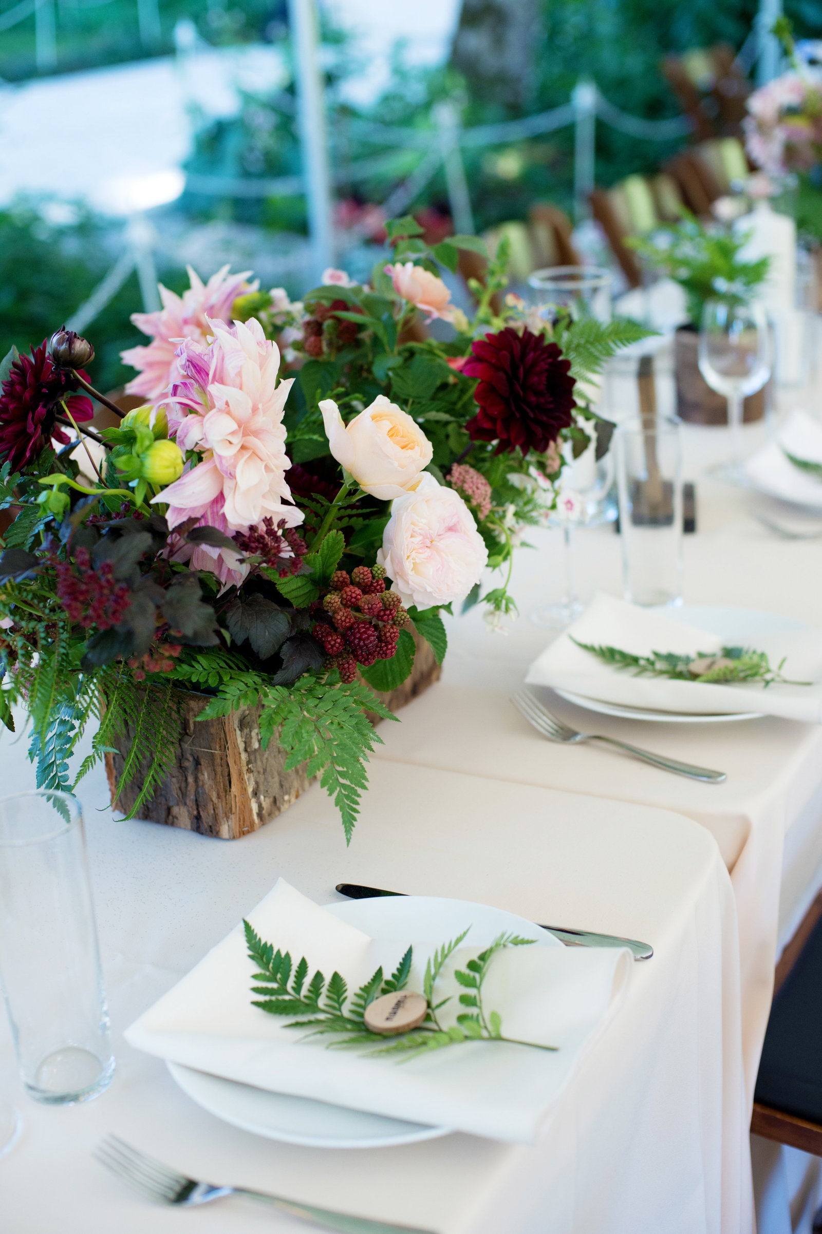 fern leaves and small wooden discs for table decor at wedding