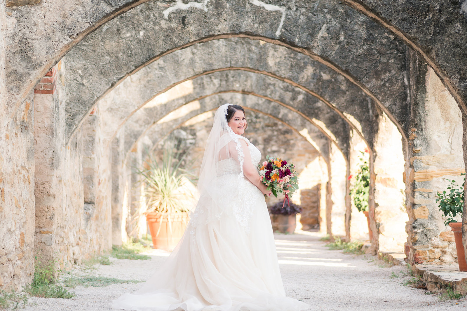 Bride in Jasmine Bridal gown smiles over her should at Mission San Jose in San Antonio Texas holding a fall floral bouquet by Eden's Echo