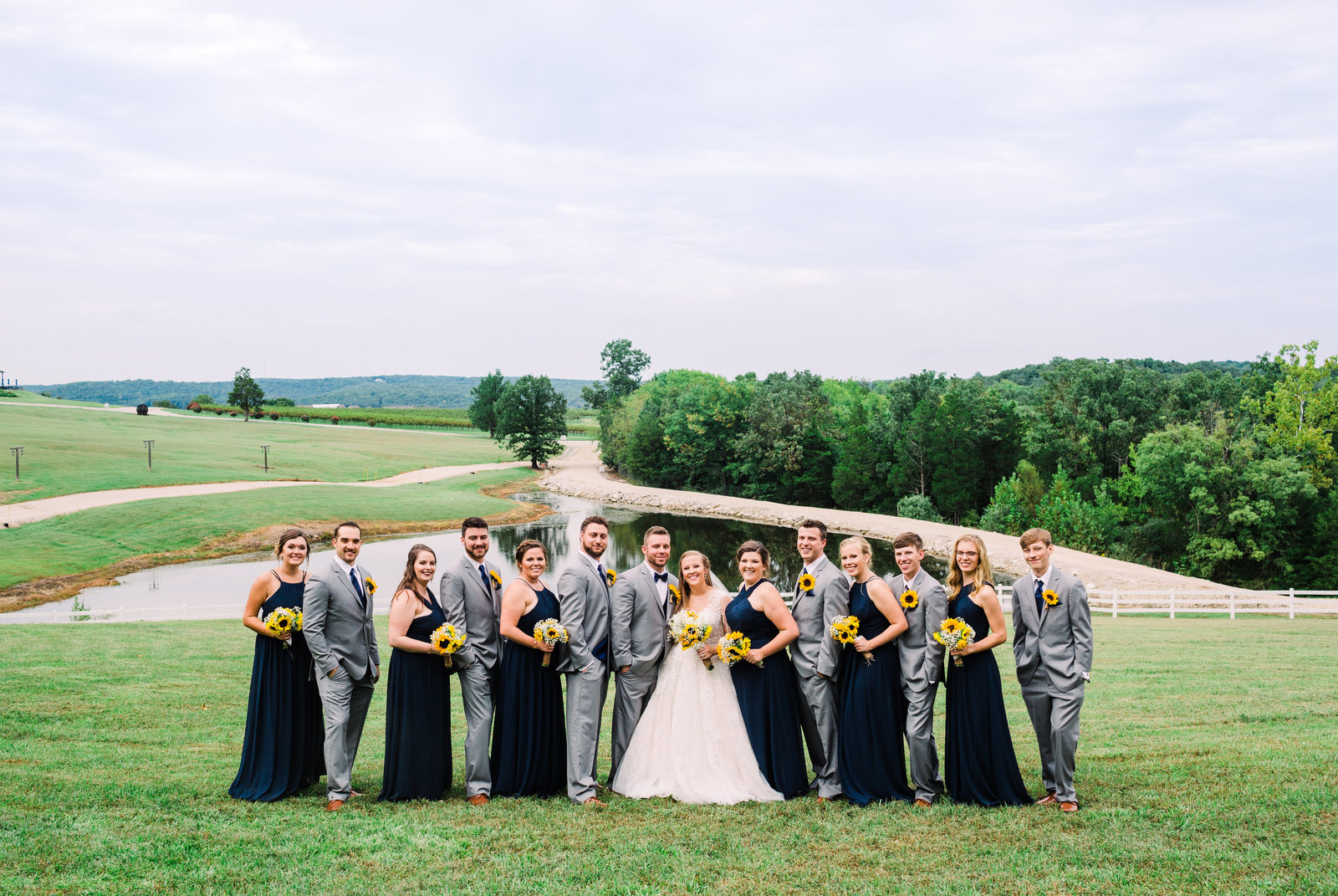 This wedding party wearing black and navy pose on a grassy hill with lake in the background at Chaumette Winery.