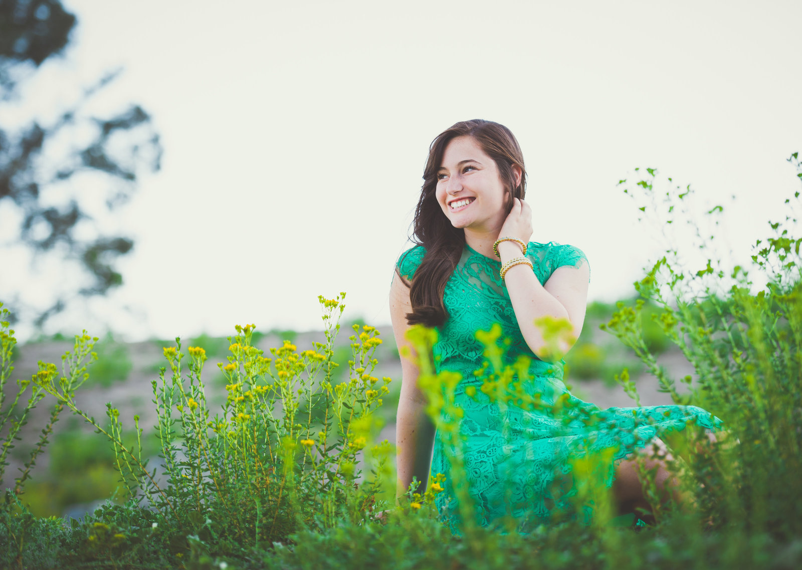 teen in green lace dress in field of flowers