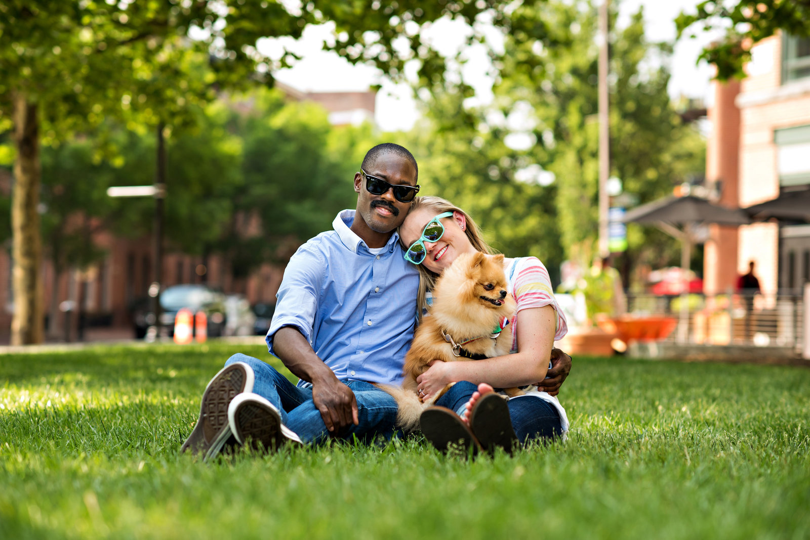 A couple lay in the park with their dog on a beautiful summer day.