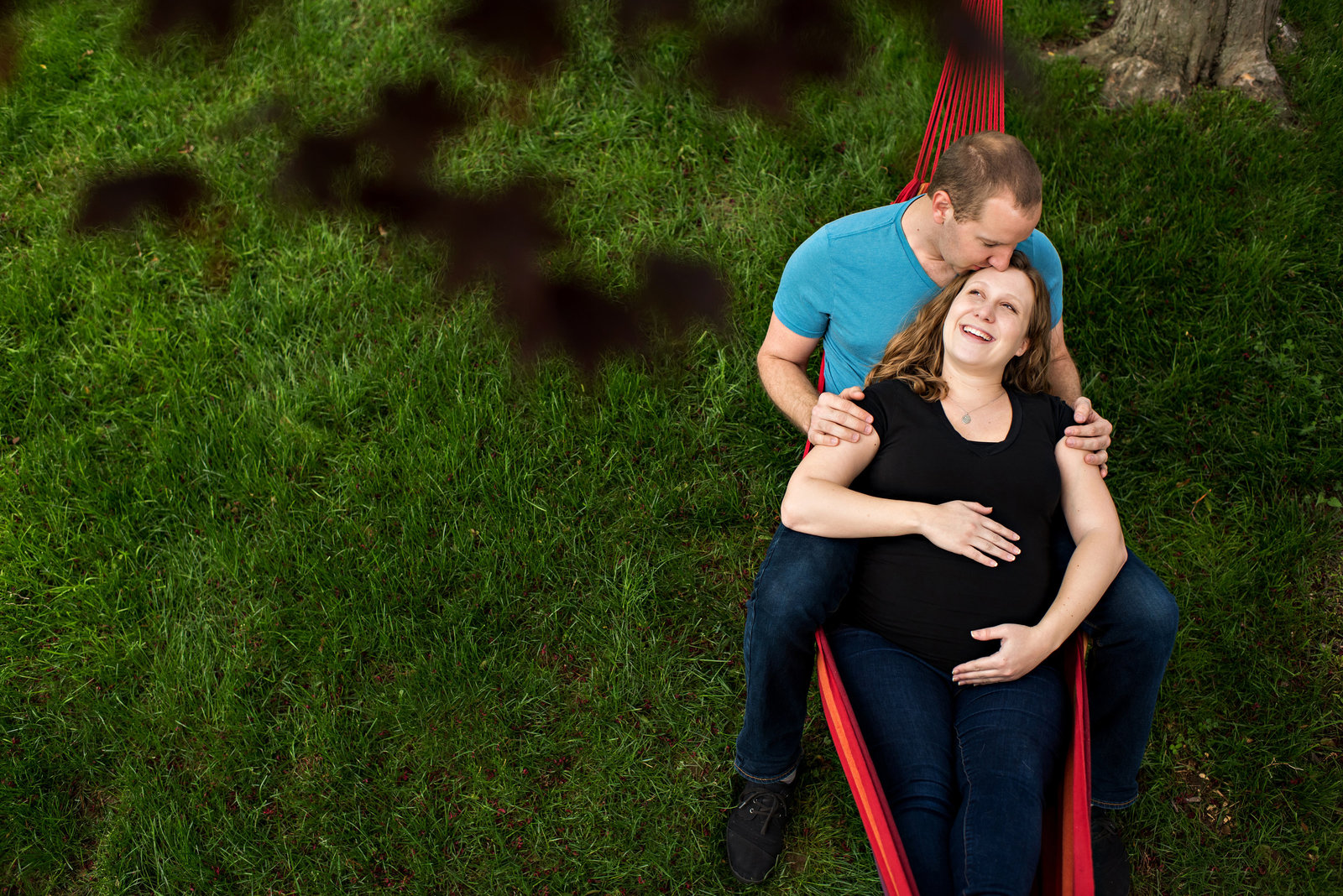 A pregnant couple lay in their hammock in the back yard during home maternity session.