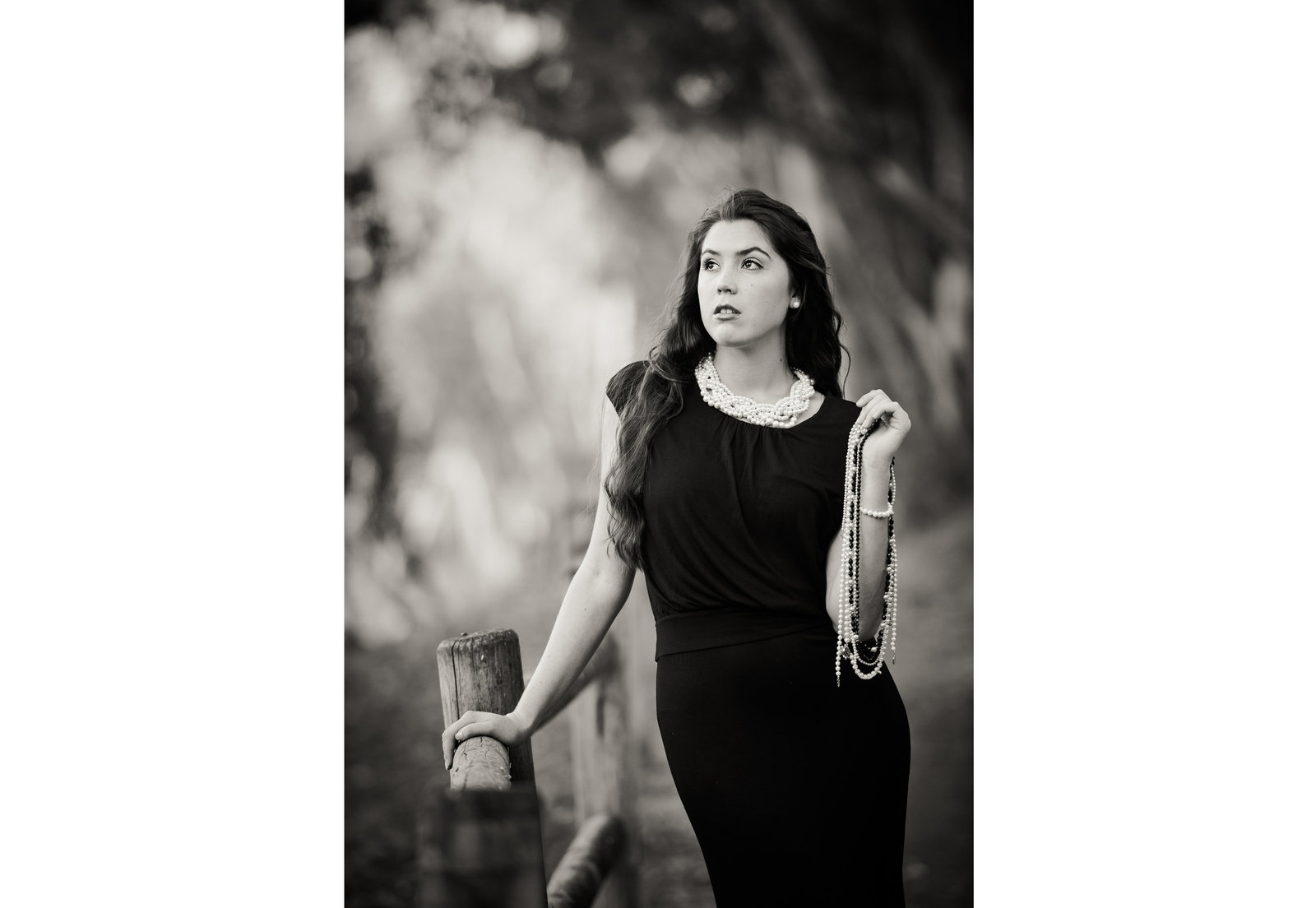 black and white of high school senior in black dress and pearls