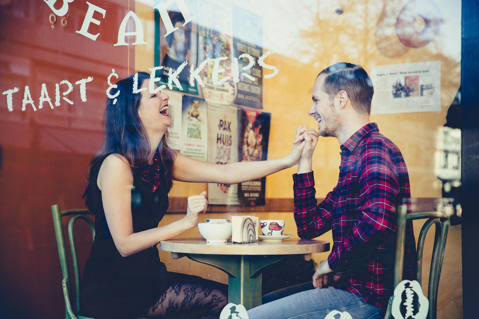 Loveshoot door het raam. Vriend met geruit overhemd laat zijn vriendin lachen. Copyright Nanda Zee-Fritse | FOTOZEE