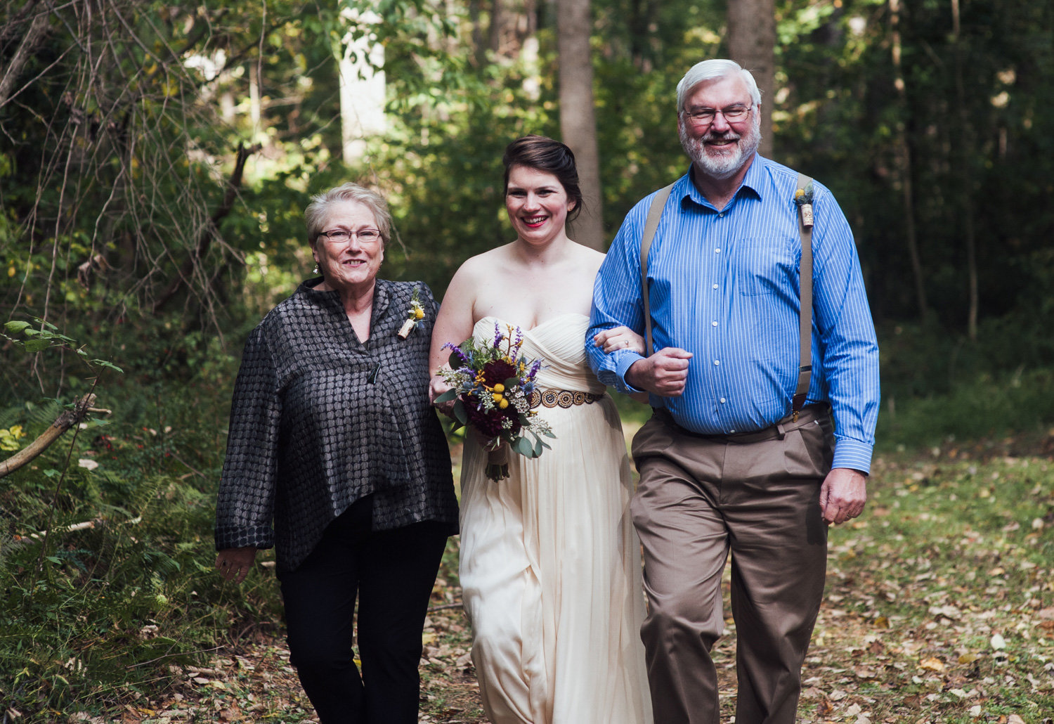 bride lead by parents to outdoor ceremony