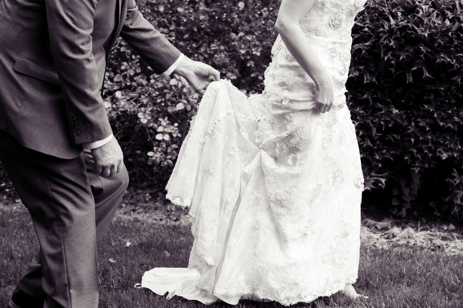 a groom holds bride's wedding dress